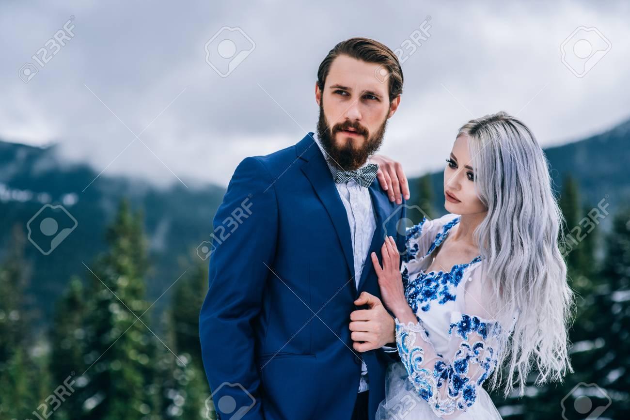 bräutigam in einem blauen anzug und braut in weiß, mit blauem muster  bestickt, kleid auf einem hintergrund von grünen pinienwäldern in den  bergen der