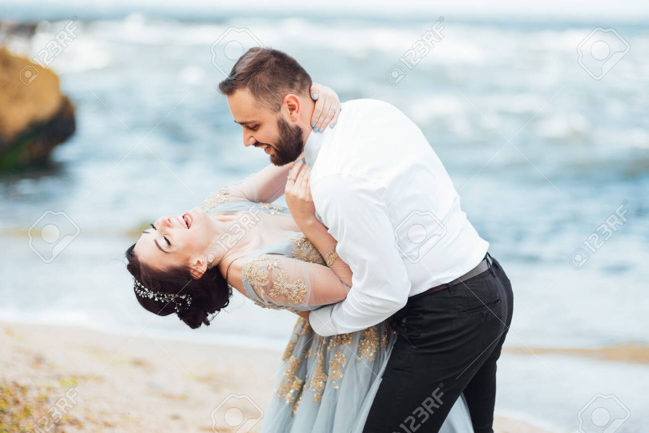 same couple with a bride in a blue dress walk along the ocean shore - 141194094