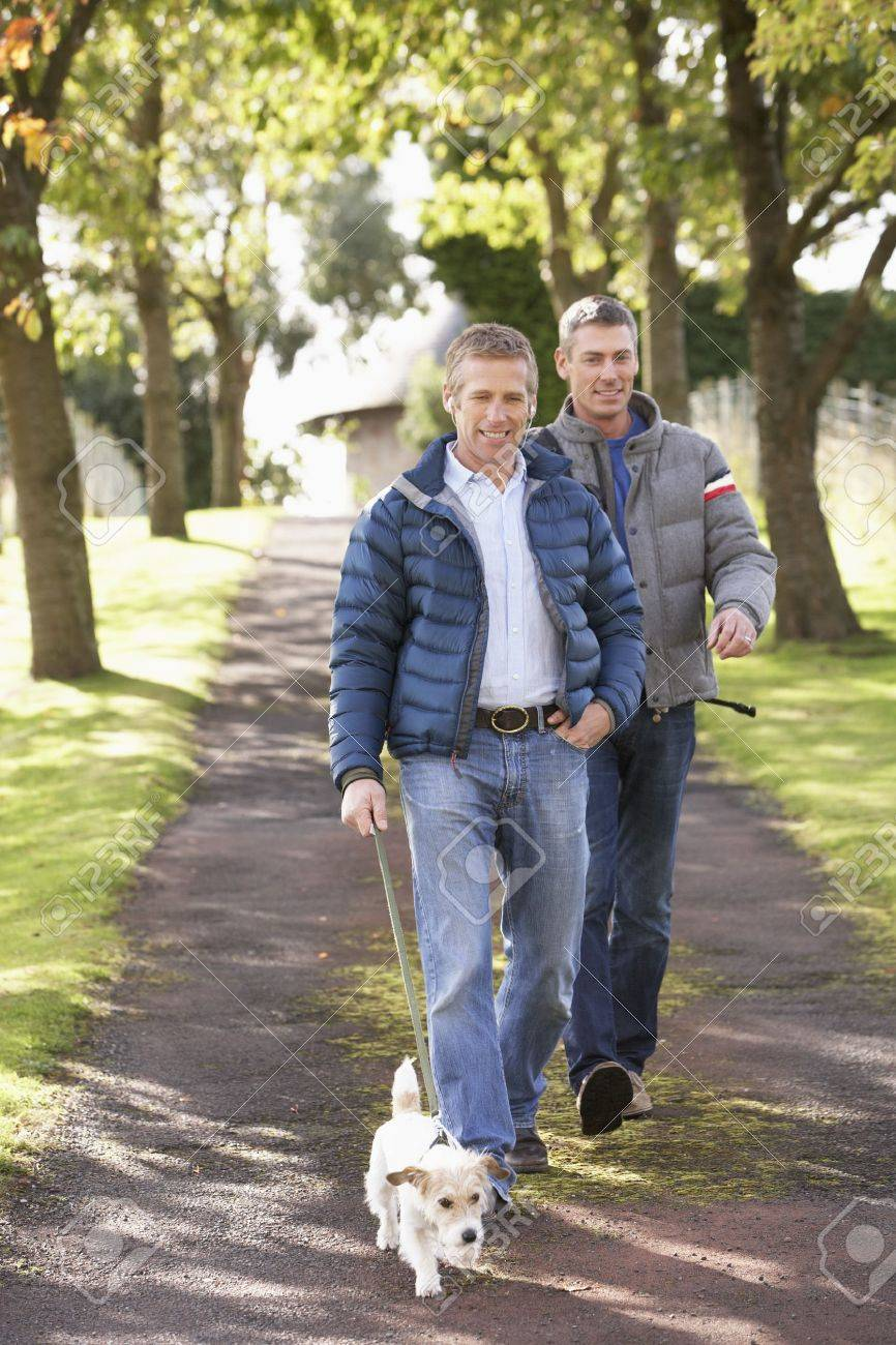 Two Male Friends Walking Dog Outdoors In Autumn Park Together Stock Photo - 7185151