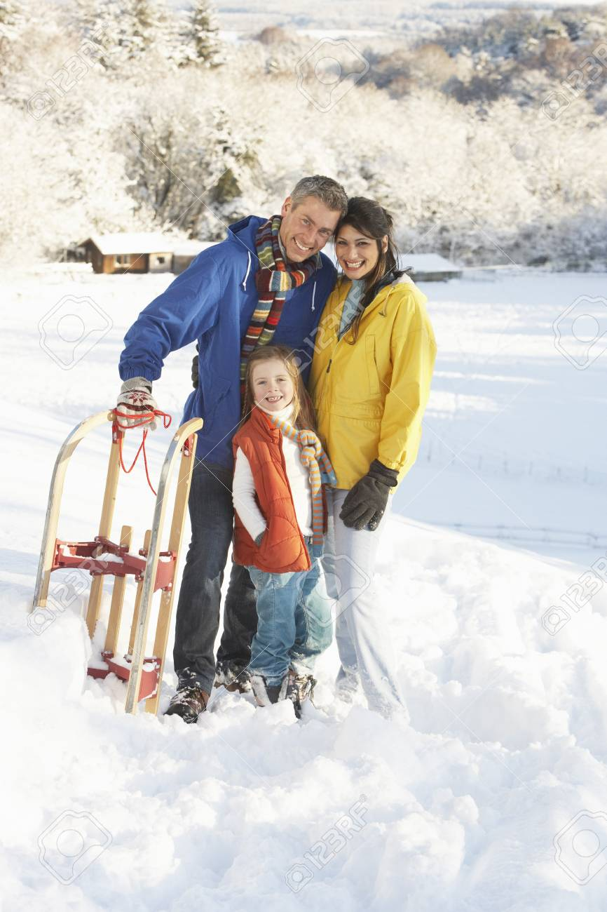 Young Family Standing In Snowy Landscape Holding Sledge Stock Photo - 7178400