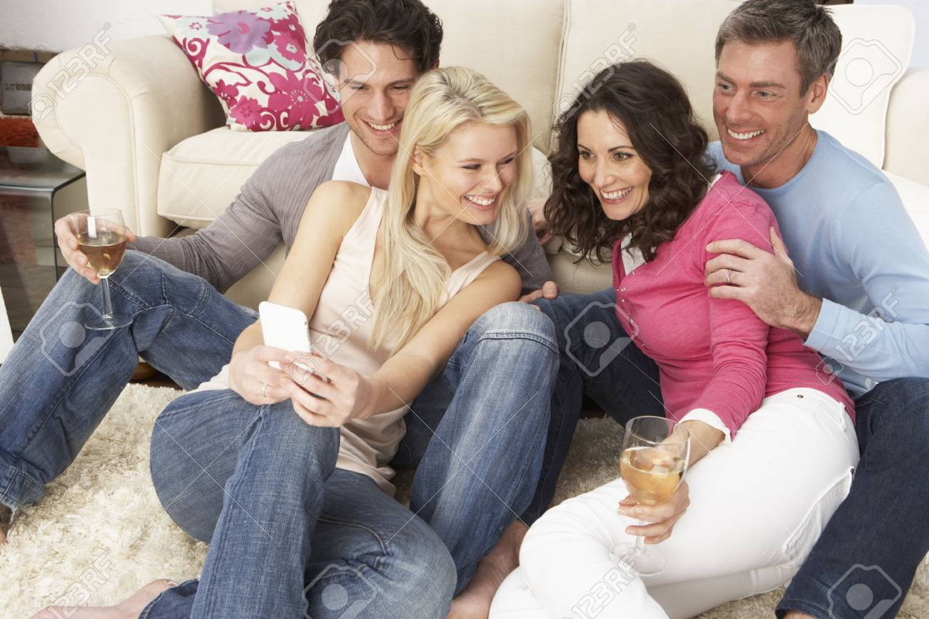 Group Of  Friends Looking At Pictures On Smartphone At Home Stock Photo - 8452864