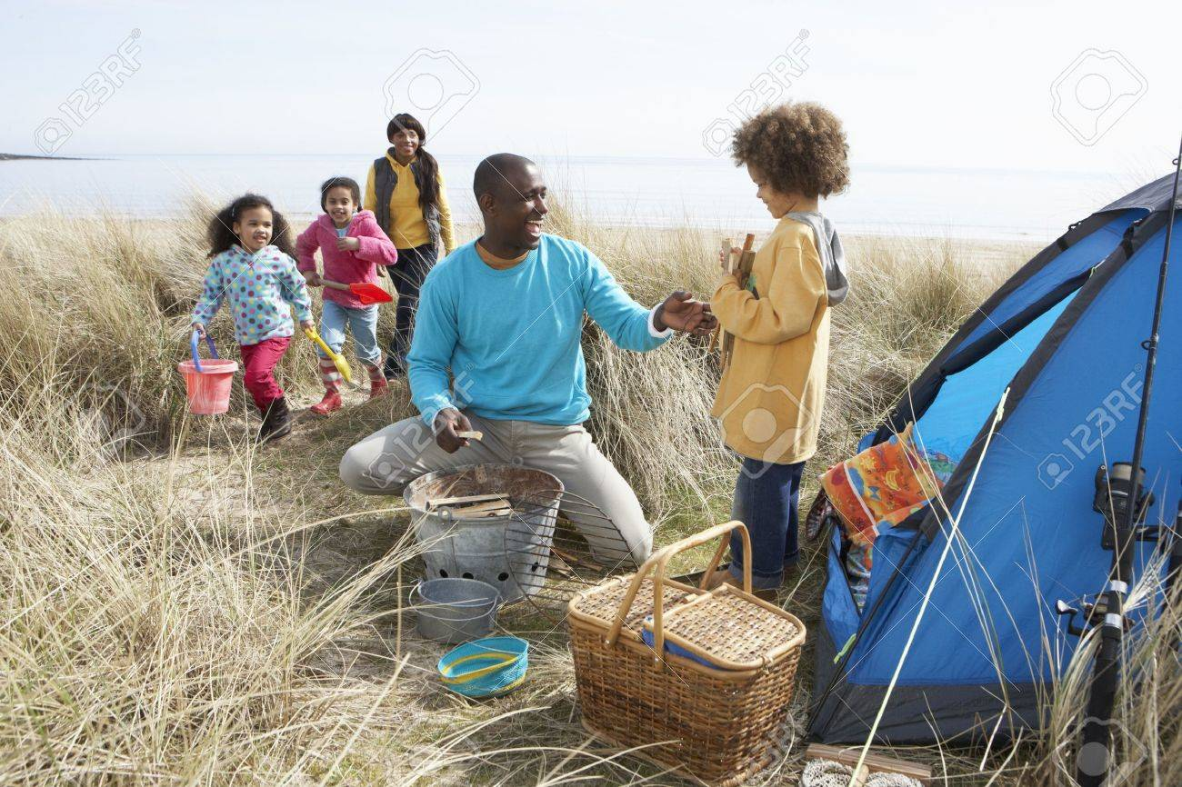 Young Family Relaxing On Beach Camping Holiday - 10199275