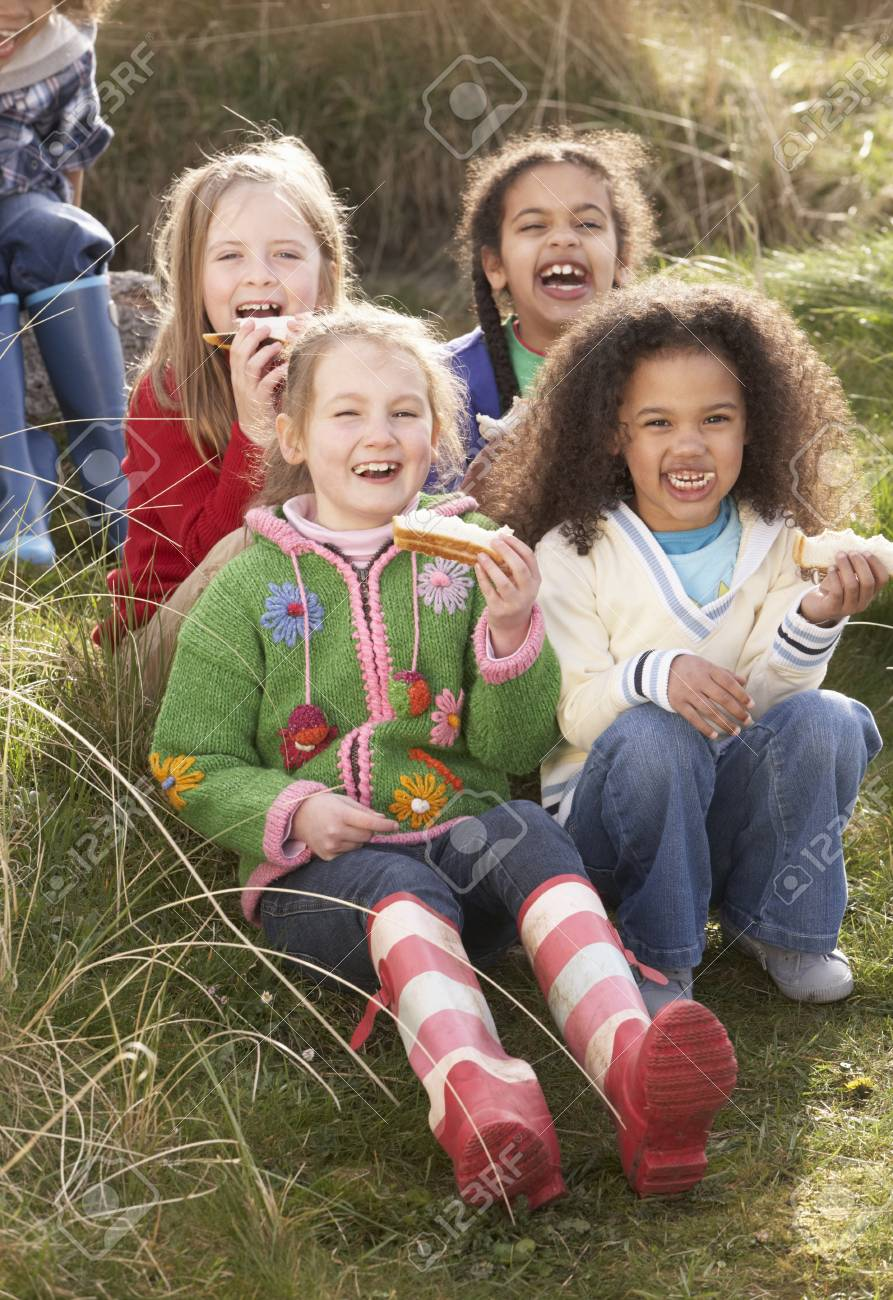 Group Of Girls Eating Cream Cakes In Field Together Stock Photo - 10199241