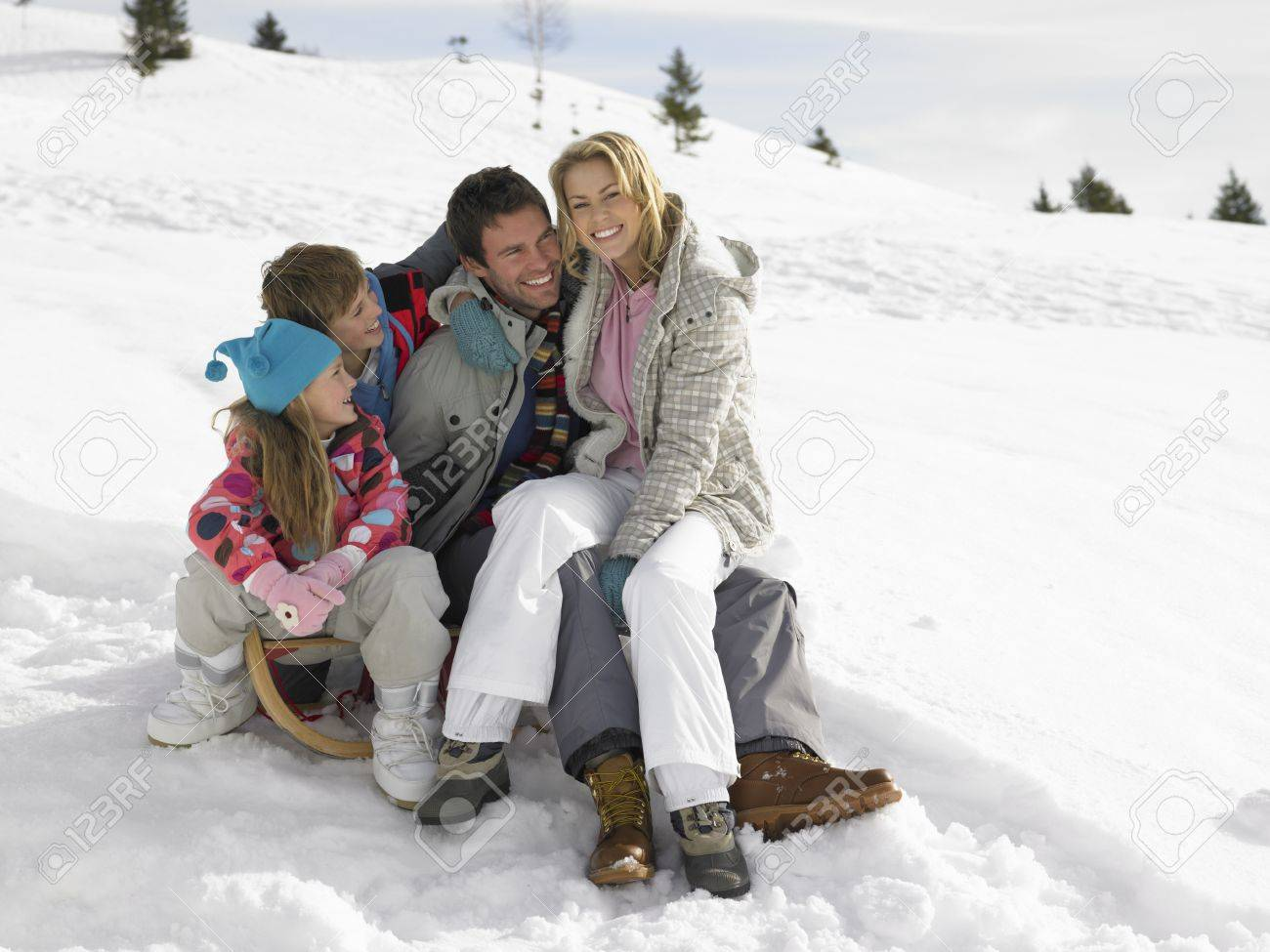 Young Family Sitting On A Sled In The Snow Stock Photo - 11246652