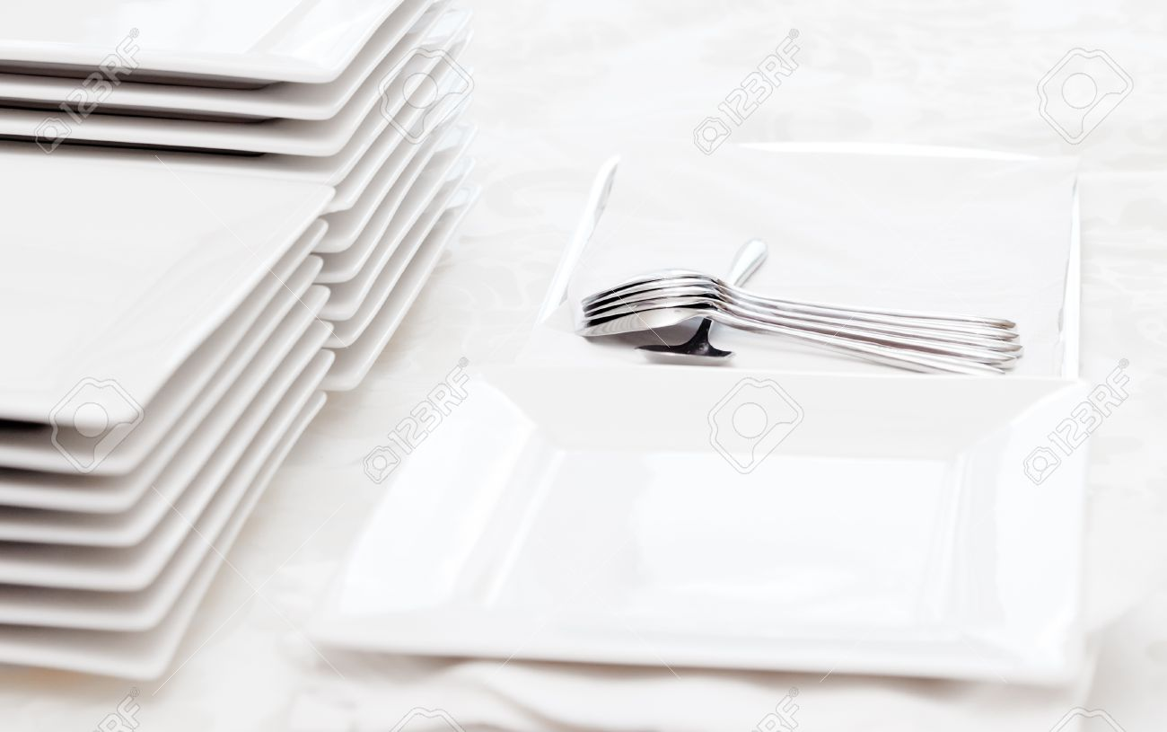 Stack of square white plates and silver spoons at a catered buffet. Stock Photo - 11614420