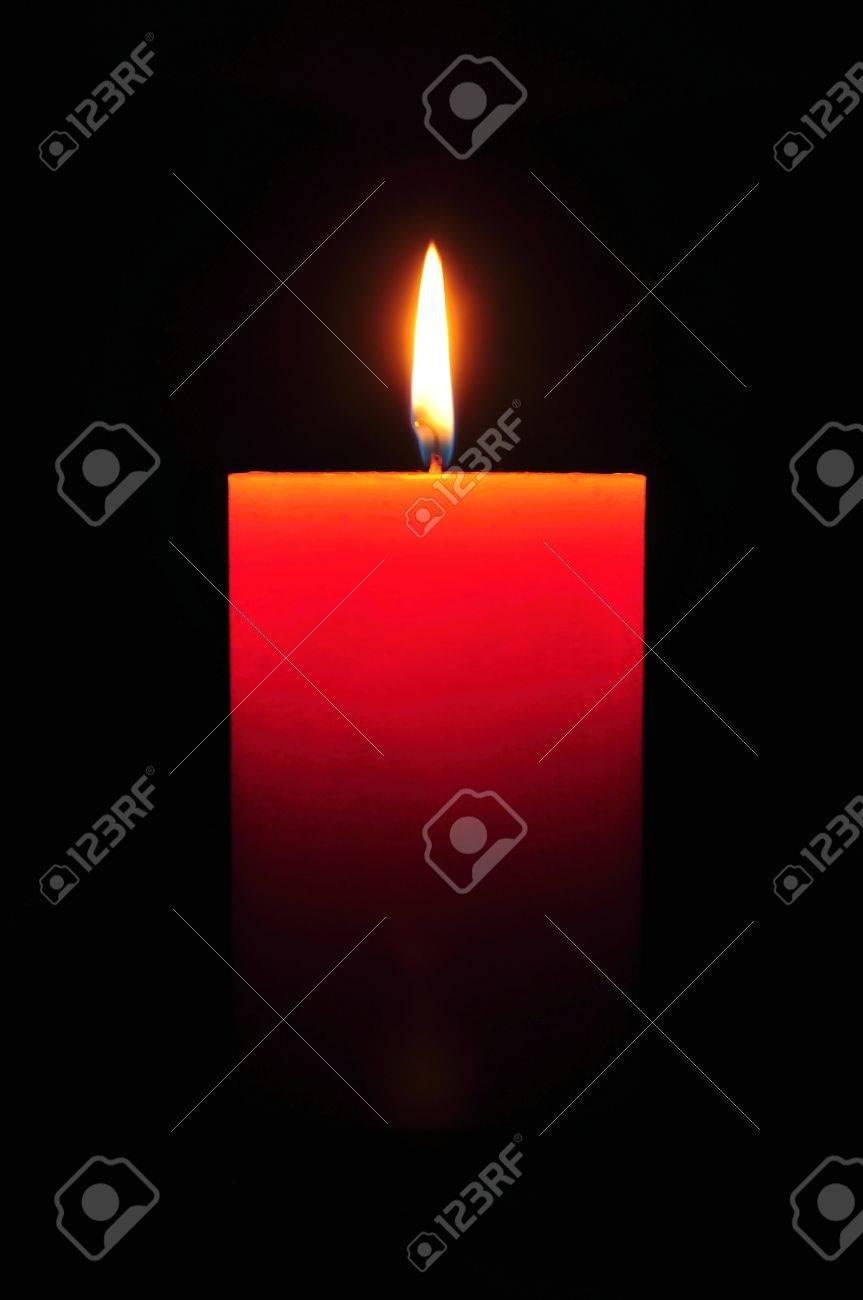 Burning large orange candle on a black background Stock Photo - 14985699