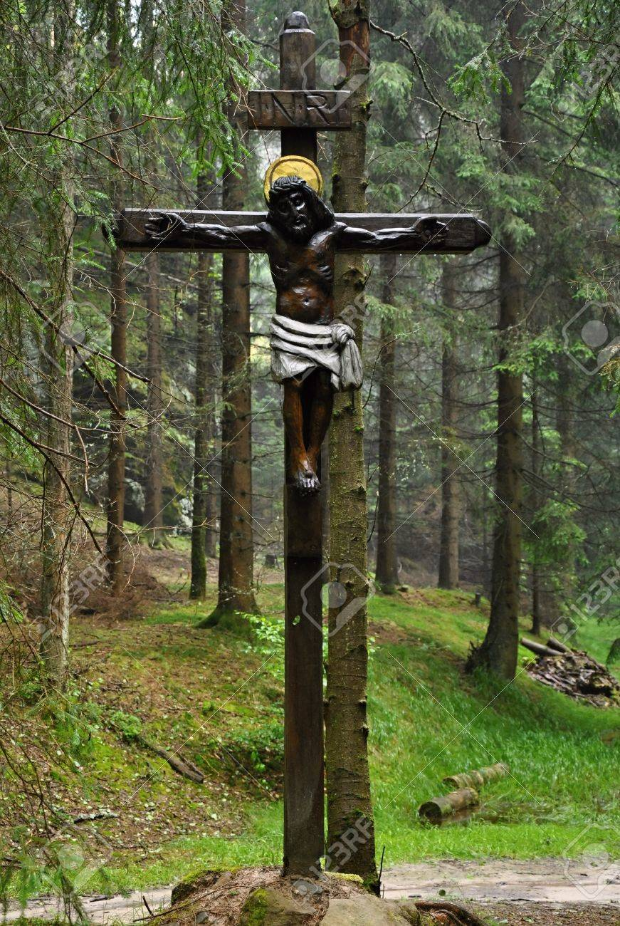 old religious cross in deep forest after rain stock photo picture