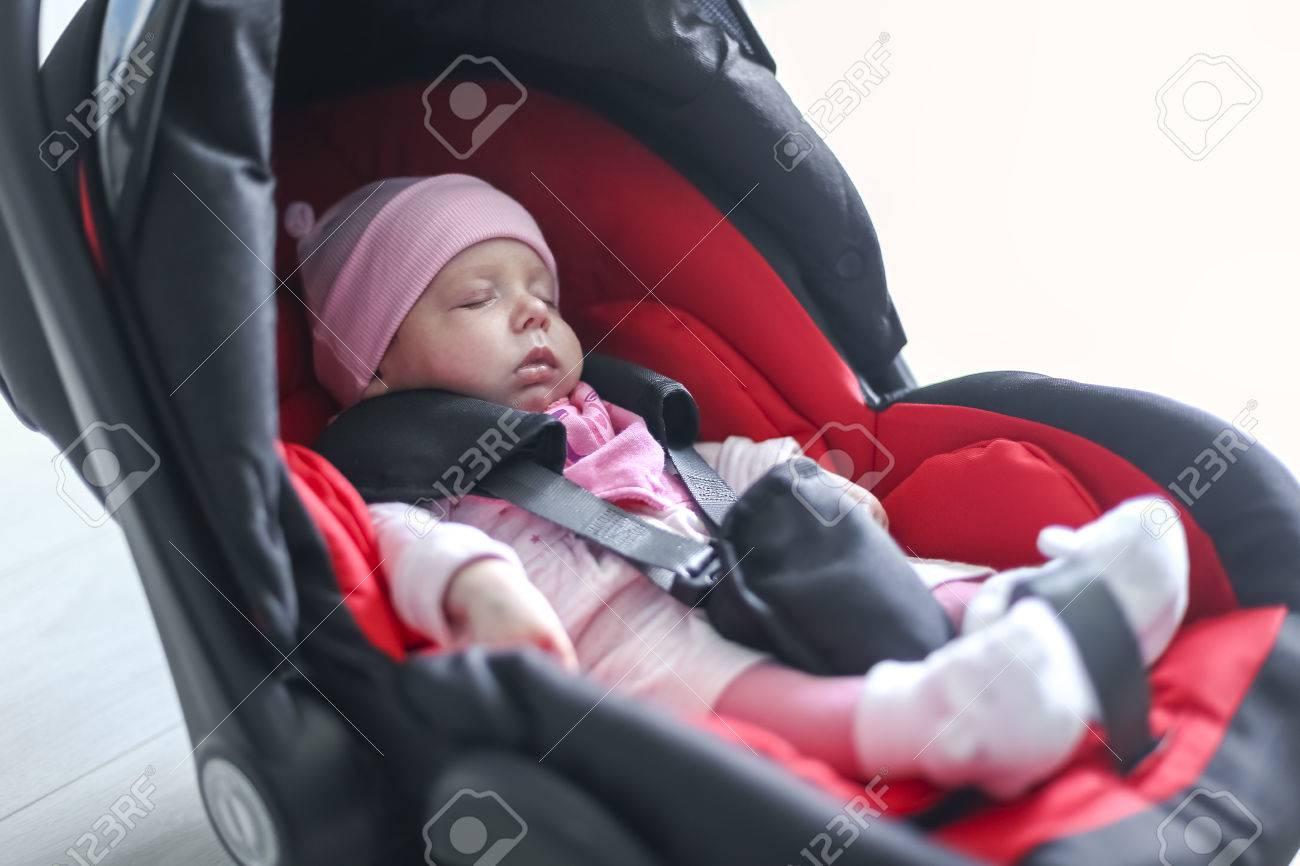 68f0dc328 El bebé recién nacido que se sienta en un asiento de coche con el cinturón  de