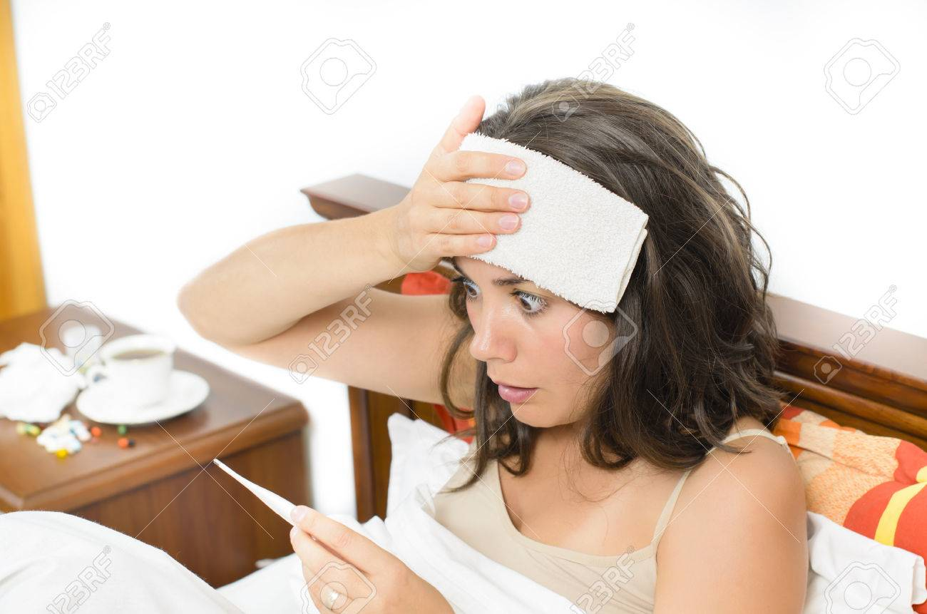 Young woman checking her temperature Stock Photo - 22283366