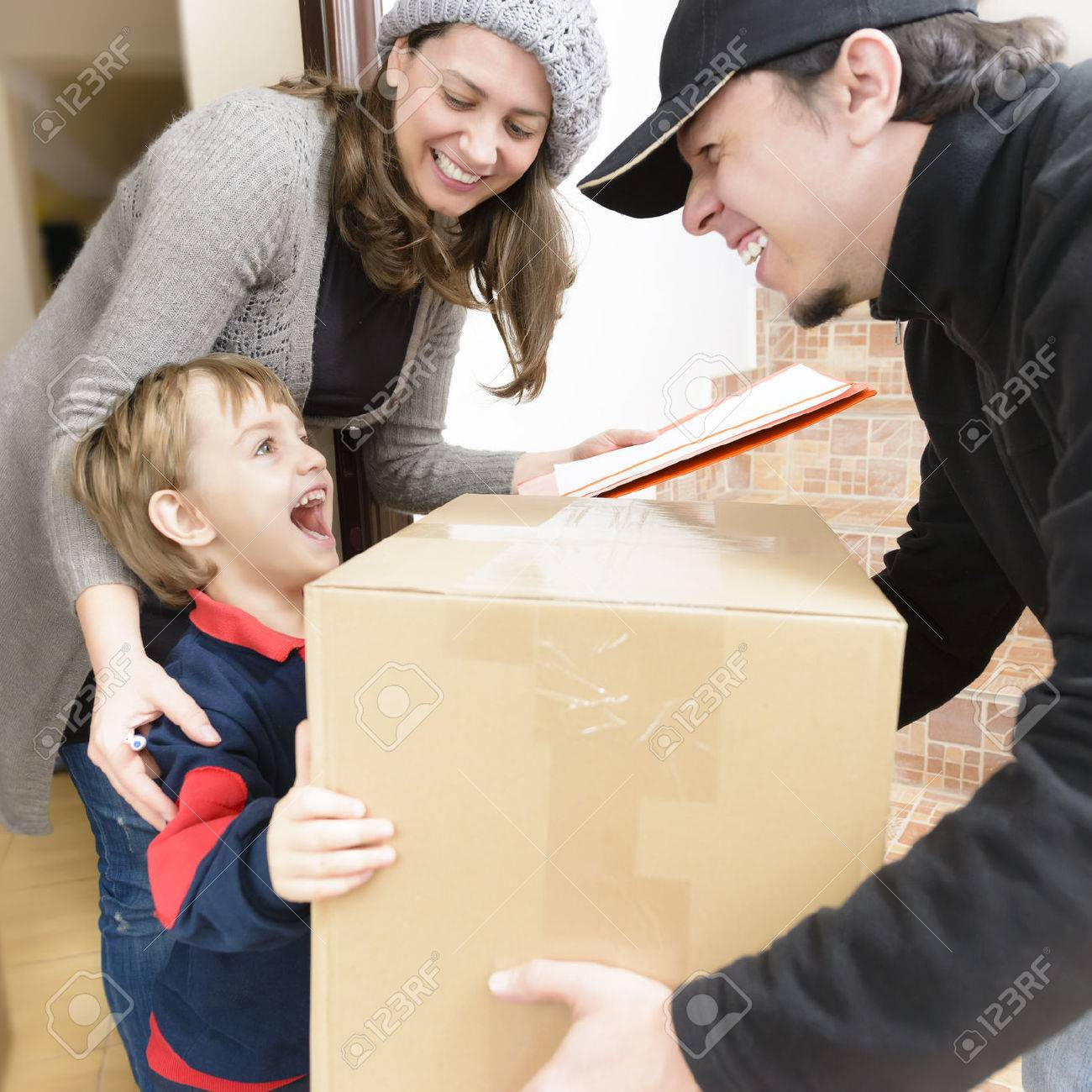 Courier Delivering a Package to a happy boy - 58927067