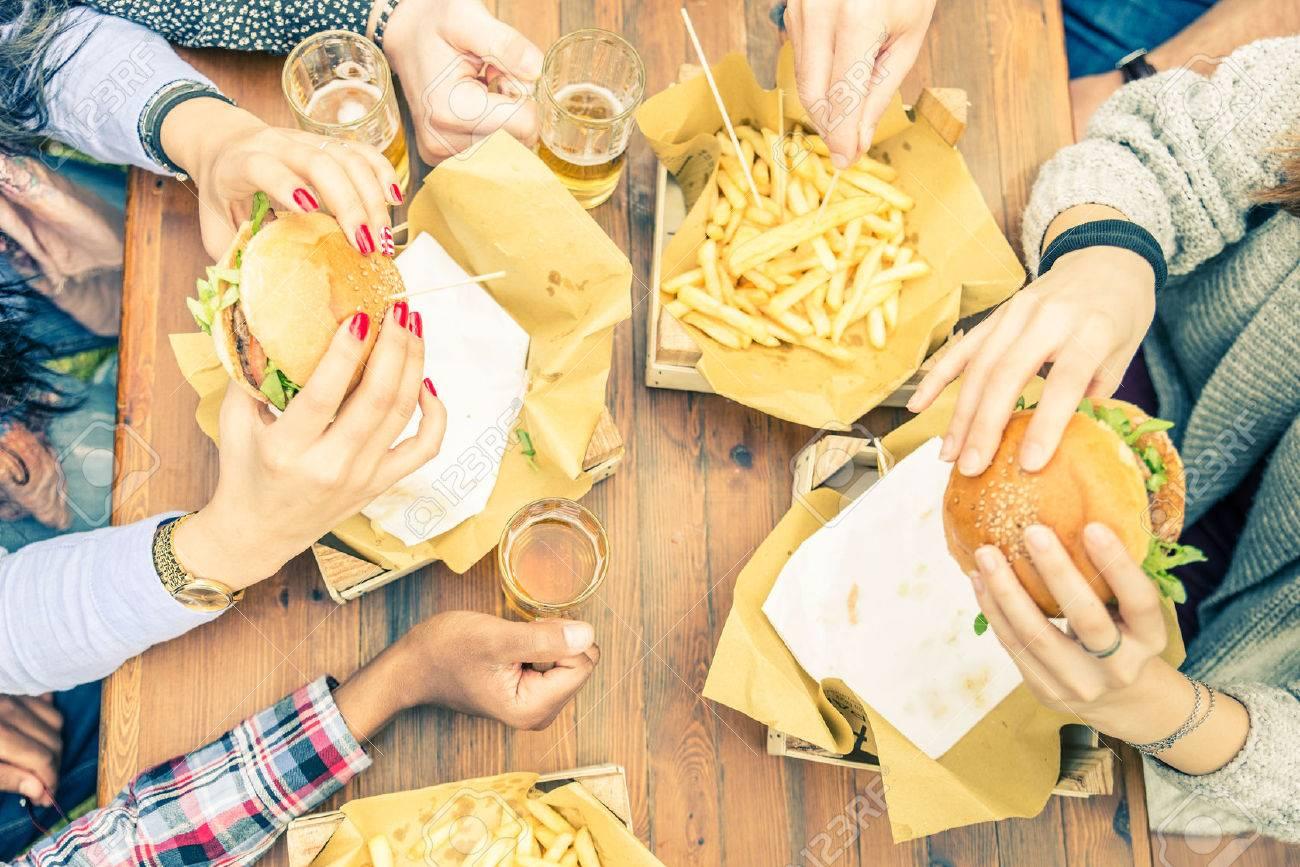 Groupe d\'amis de grillage verres de bière et de manger au fast food - Les  gens heureux faire la fête et manger dans la maison de jardin - Les jeunes  ...