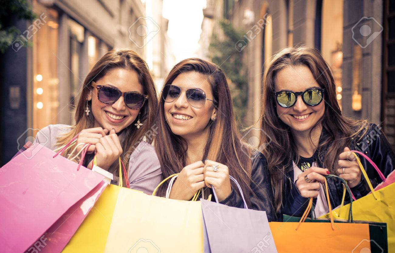 Smiling Girls With Shopping Bags. Three Friends Making Shopping ...