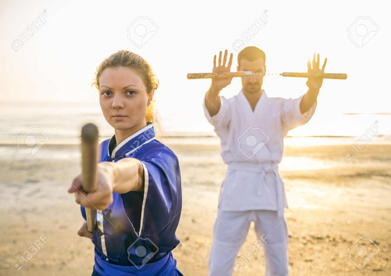 Two martial arts athletes training with weapons on the beach