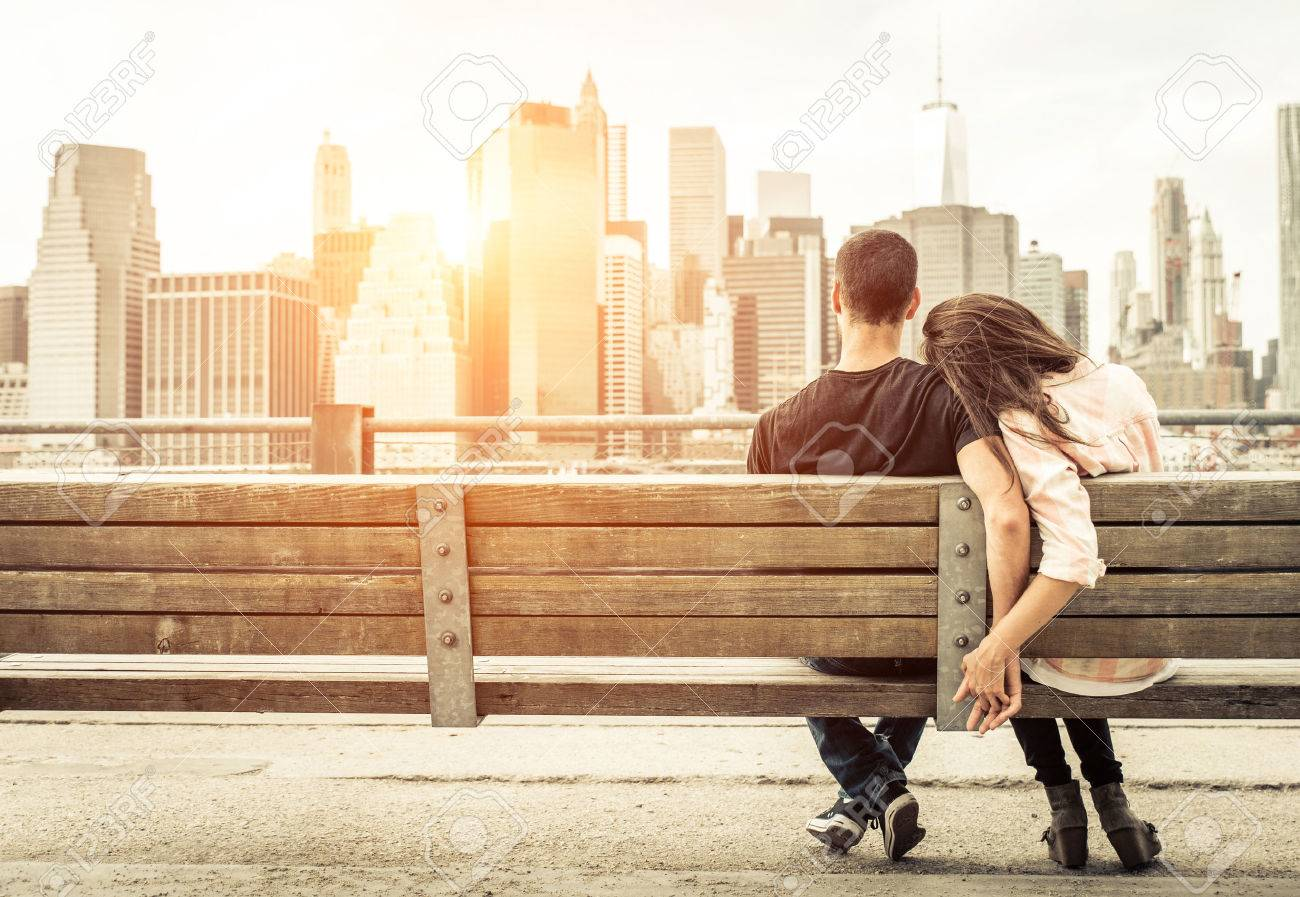 couple relaxing on New york bench in front of the skyline at sunset time. concept about love,relationship, and travel Stock Photo - 47114383