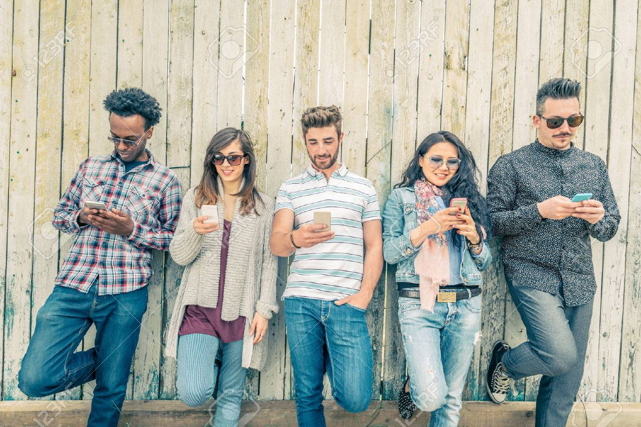 Young people looking down at cellular phone - Teenagers leaning on a wall and texting with their smartphones - Concepts about technology and global communication Stock Photo - 48007791
