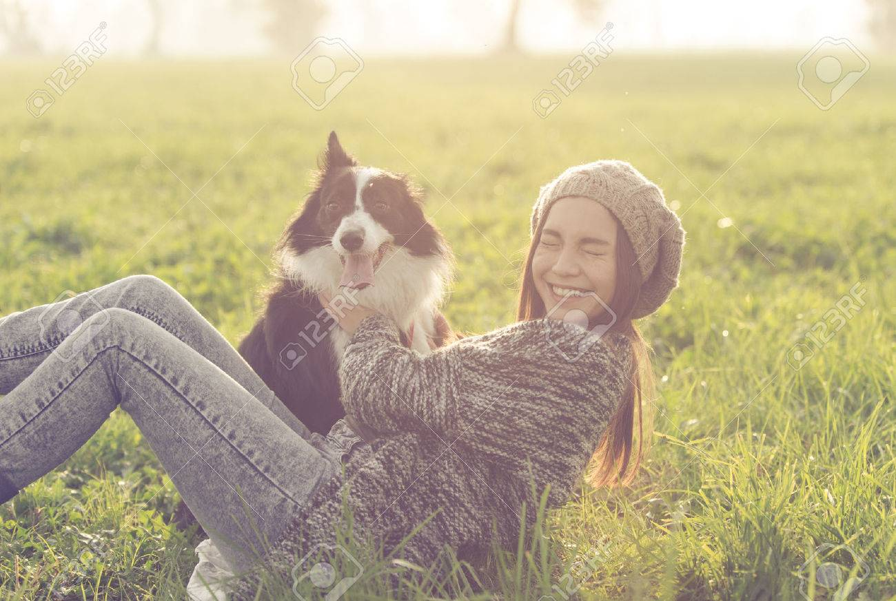 Young woman playing with her border collie dog. concept aout animals and people Stock Photo - 50428939