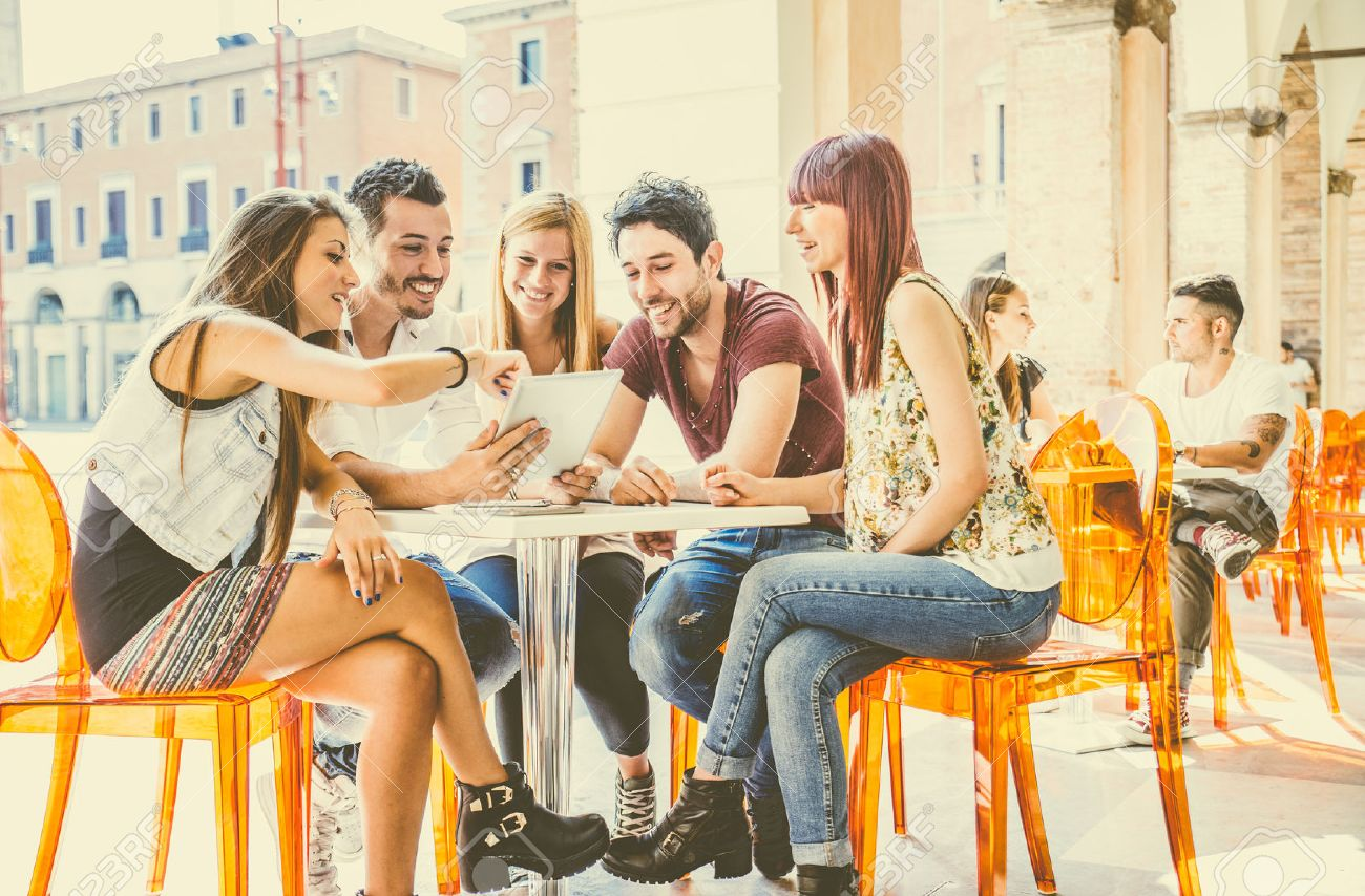 Group of students sitting in a cafe bar looking at tablet - Young cheerful friends having fun with portable computer - Active people watching a funny streaming movie online - 50576712