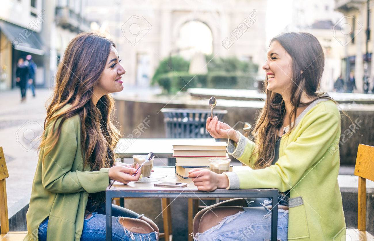 Two pretty girlfriends laughing while sitting in a bar outdoors - 50576322