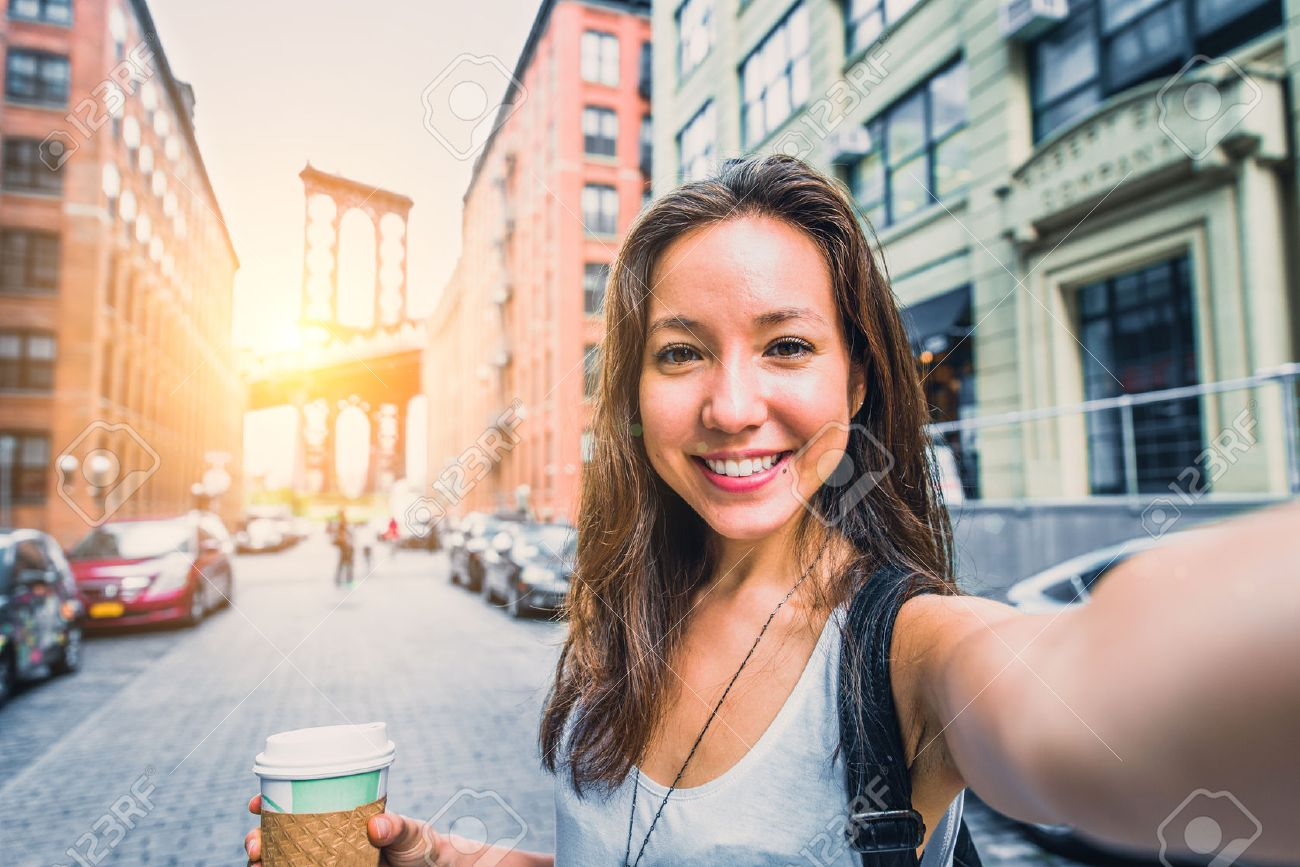 Pretty mixed race woman taking a selfie in New York, Brooklyn Bridge in the background - Beautiful girl walking on the streets of NY and photographing some landmarks Stock Photo - 52140280