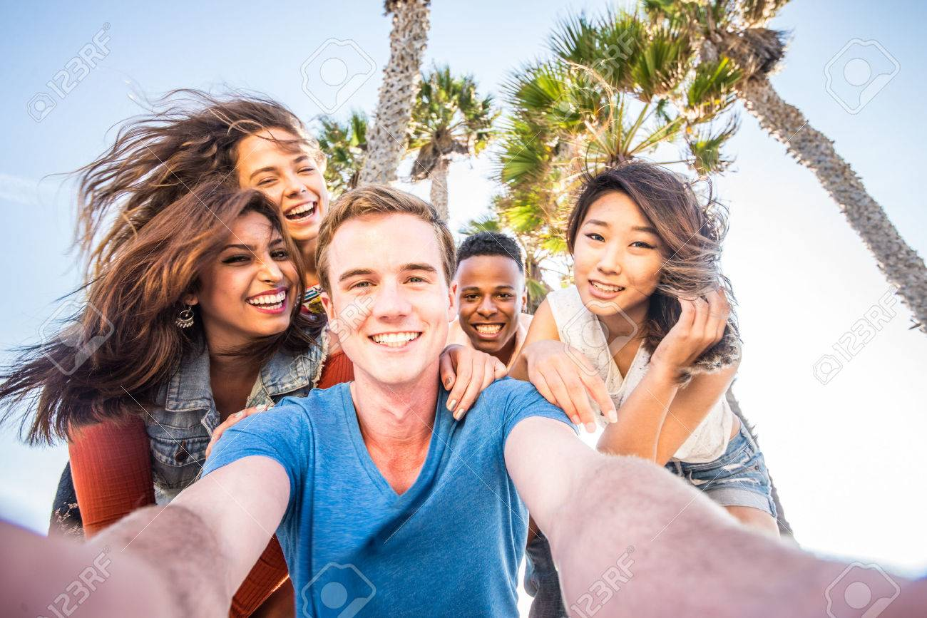 Multi-ethnic group of friends taking a self portrait picture with a camera phone - Cheerful people of diverse ethnics having fun and partying outdoors on a summer vacation - 52900010