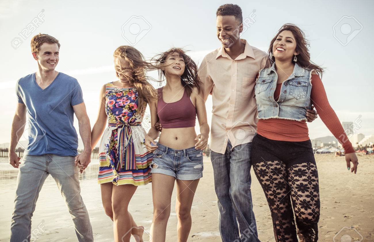 mixed race group of friends walking in santa monica beach stock