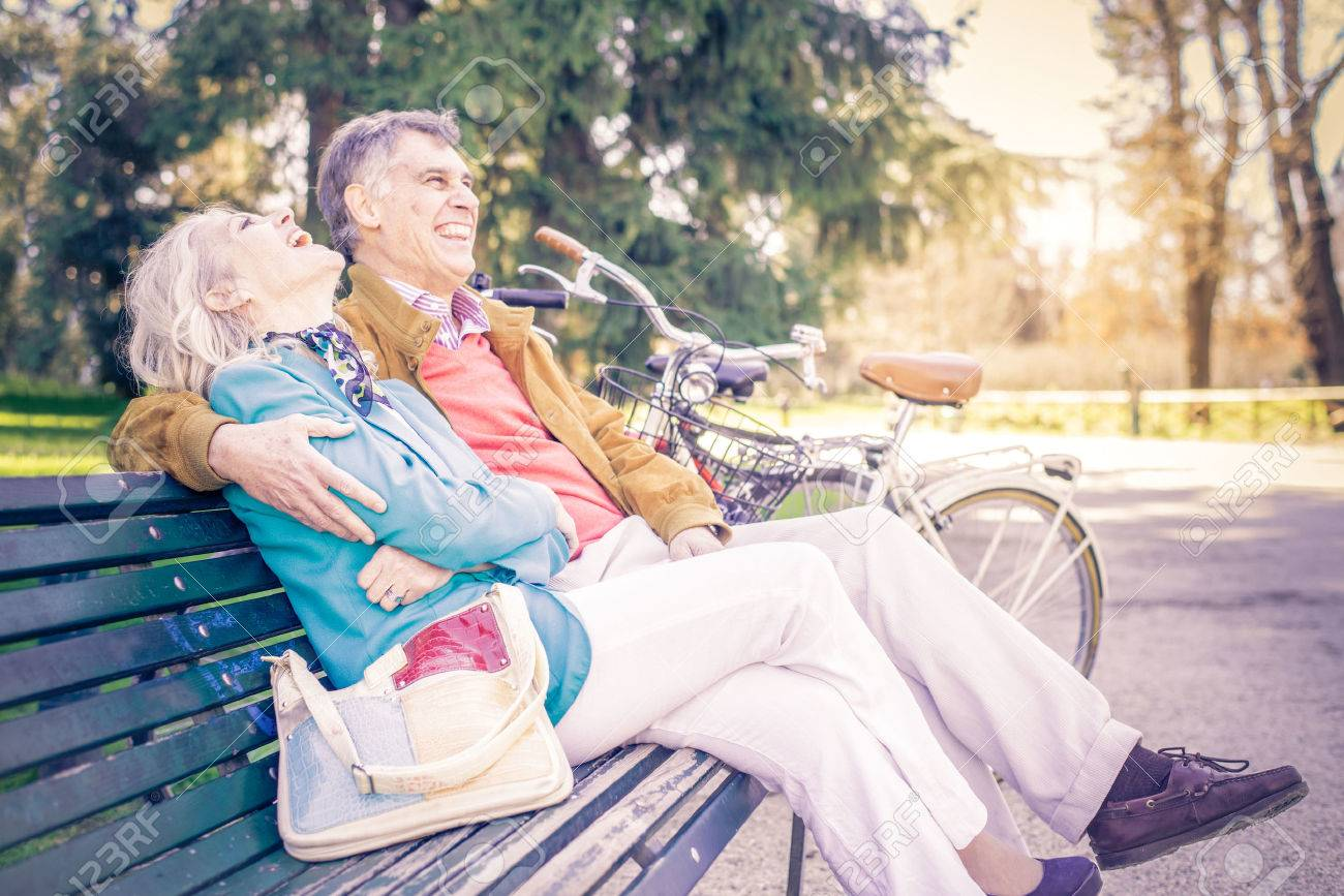Senior cheerful couple sitting on a bench in a park - Two pensioners having fun together outdoors - 54805937