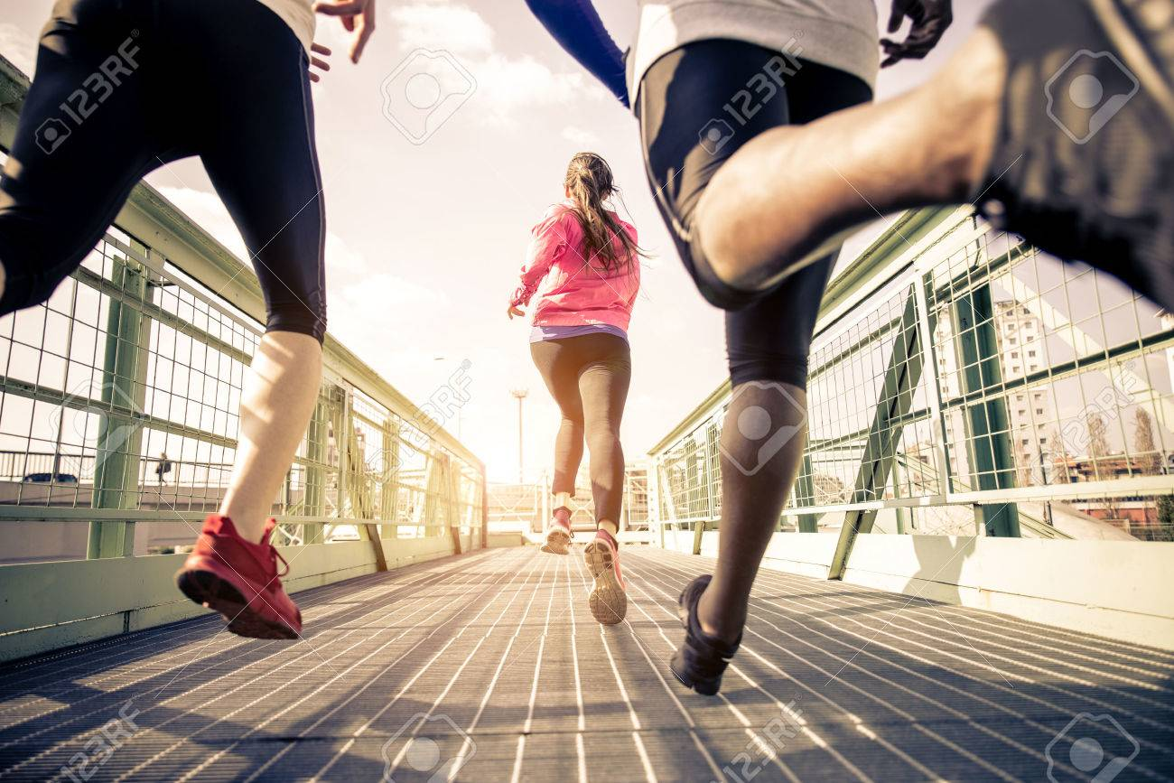 Three runners sprinting outdoors - Sportive people training in a urban area, healthy lifestyle and sport concepts - 54232441