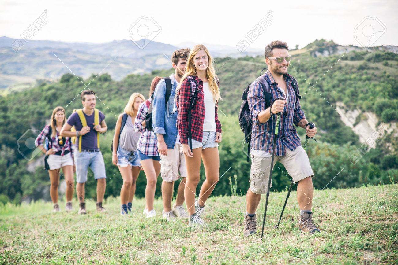 Group Of Hikers Walking In The Nature Friends Taking An Excursion On A Mountain