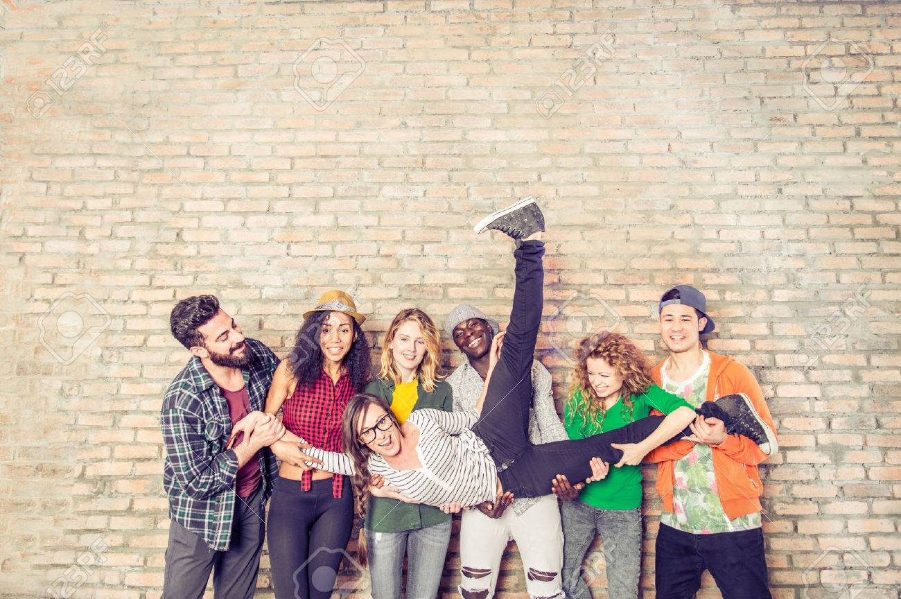Group portrait of multi-ethnic boys and girls with colorful fashionable clothes holding friend in hands and posing on a brick wall - Urban style people having fun, studio shot - Concepts about youth and togetherness - 57812372