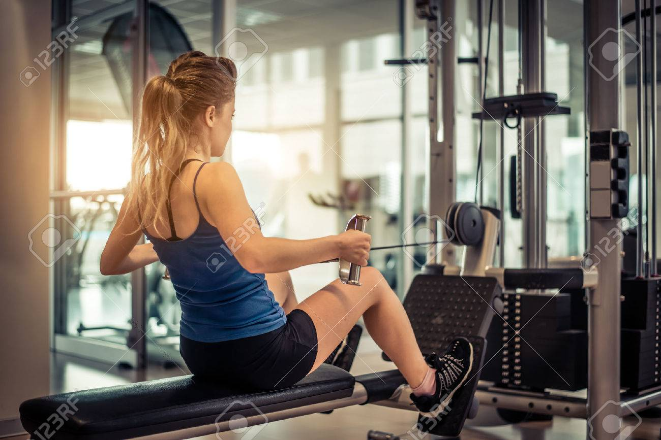 Woman training her back and shoulder with weight machine in a gym - 57813092