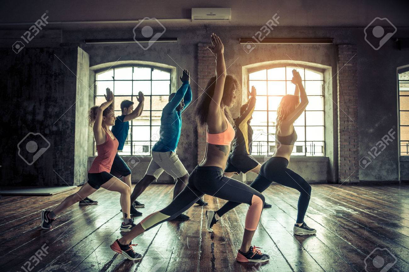 Group of sportive people in a gym training - Multiracial group of athletes stretching before starting a workout session - 57814540
