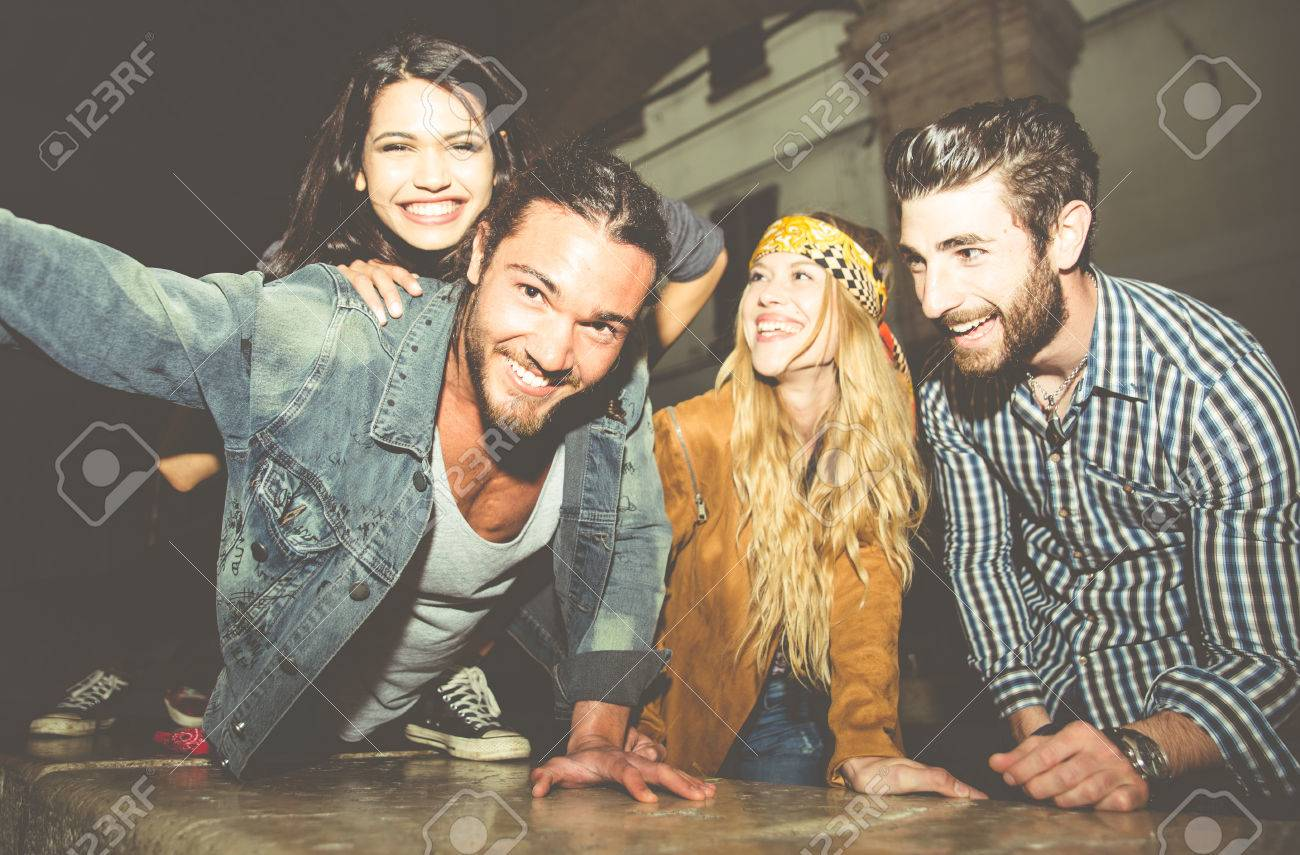 Group of friends sitting on the stairs and taking selfie. Having fun in the night outdoor - 59039376