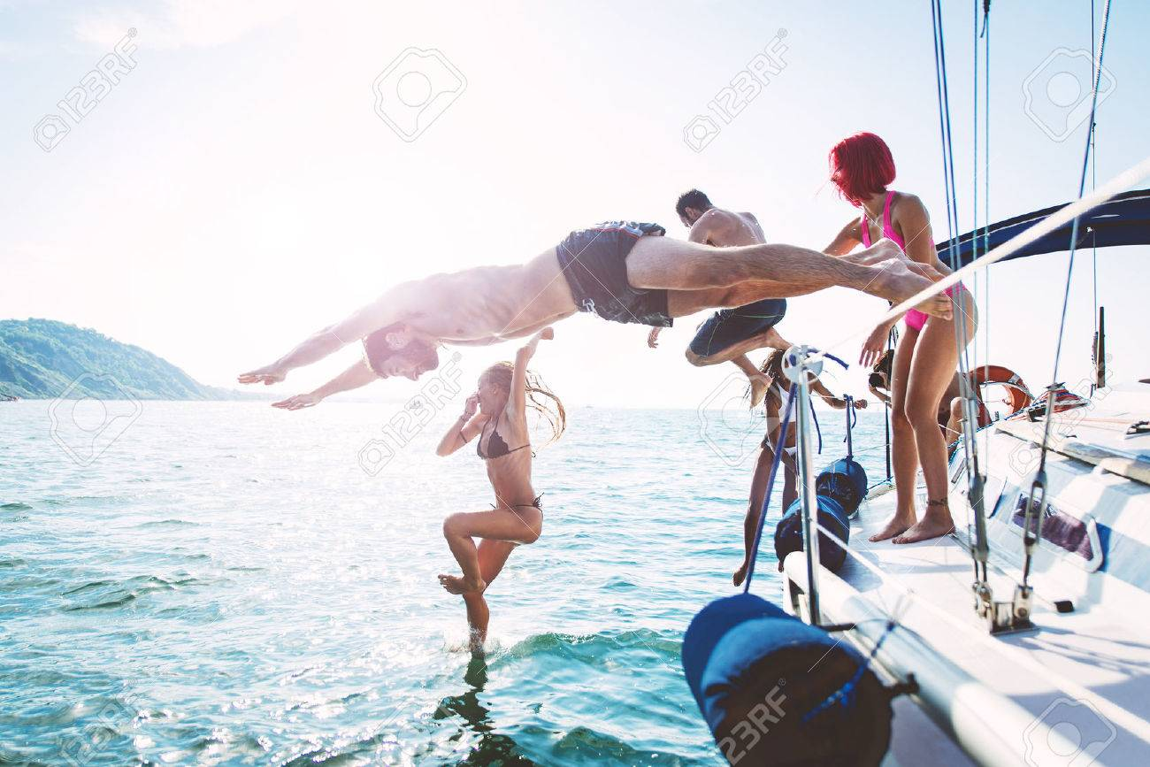 group of friends diving in the water during a boat excursion - 64360881