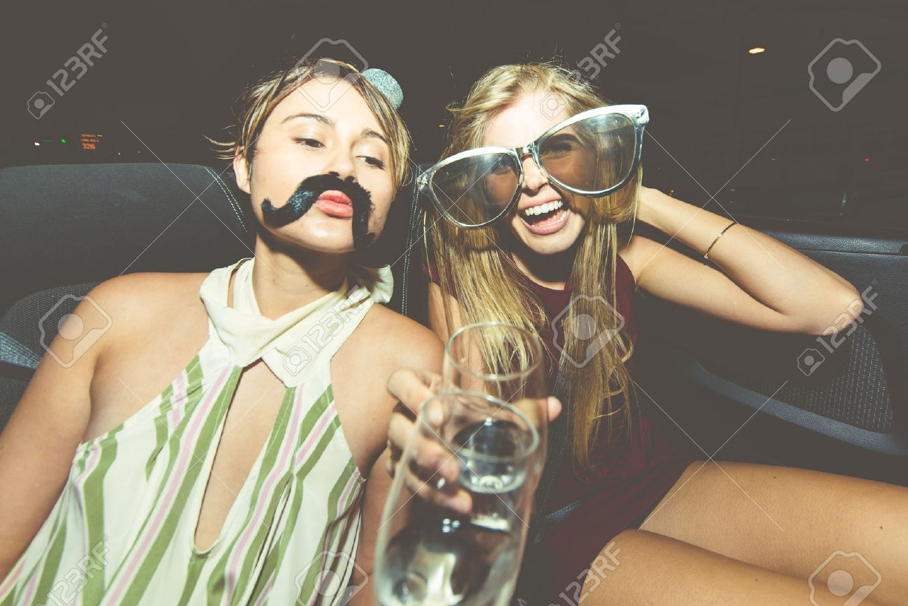 Party girls celebrate in Hollywood drinking champagne on a covertible car - 65092116