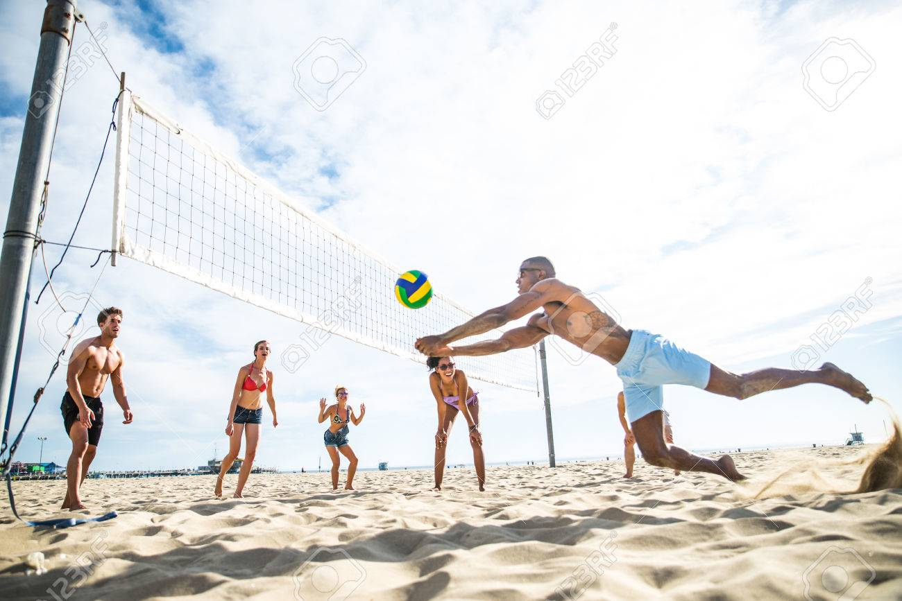Group of friends playing beach volley - Multi-ethic group of people having fun on the beach - 71078394