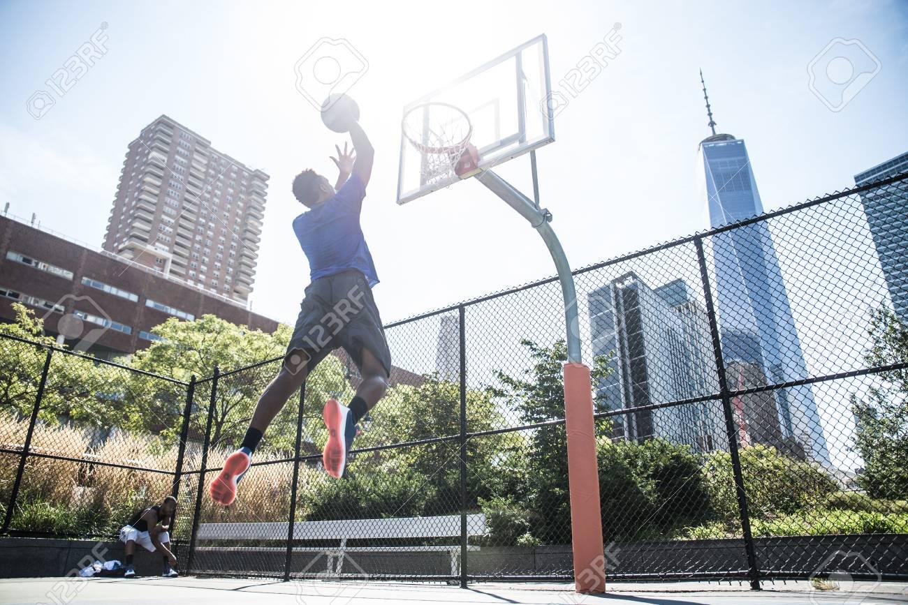 Afroamerican athlethe jouer en plein air basket joueur de basket ball dunk sur le terrain à New York