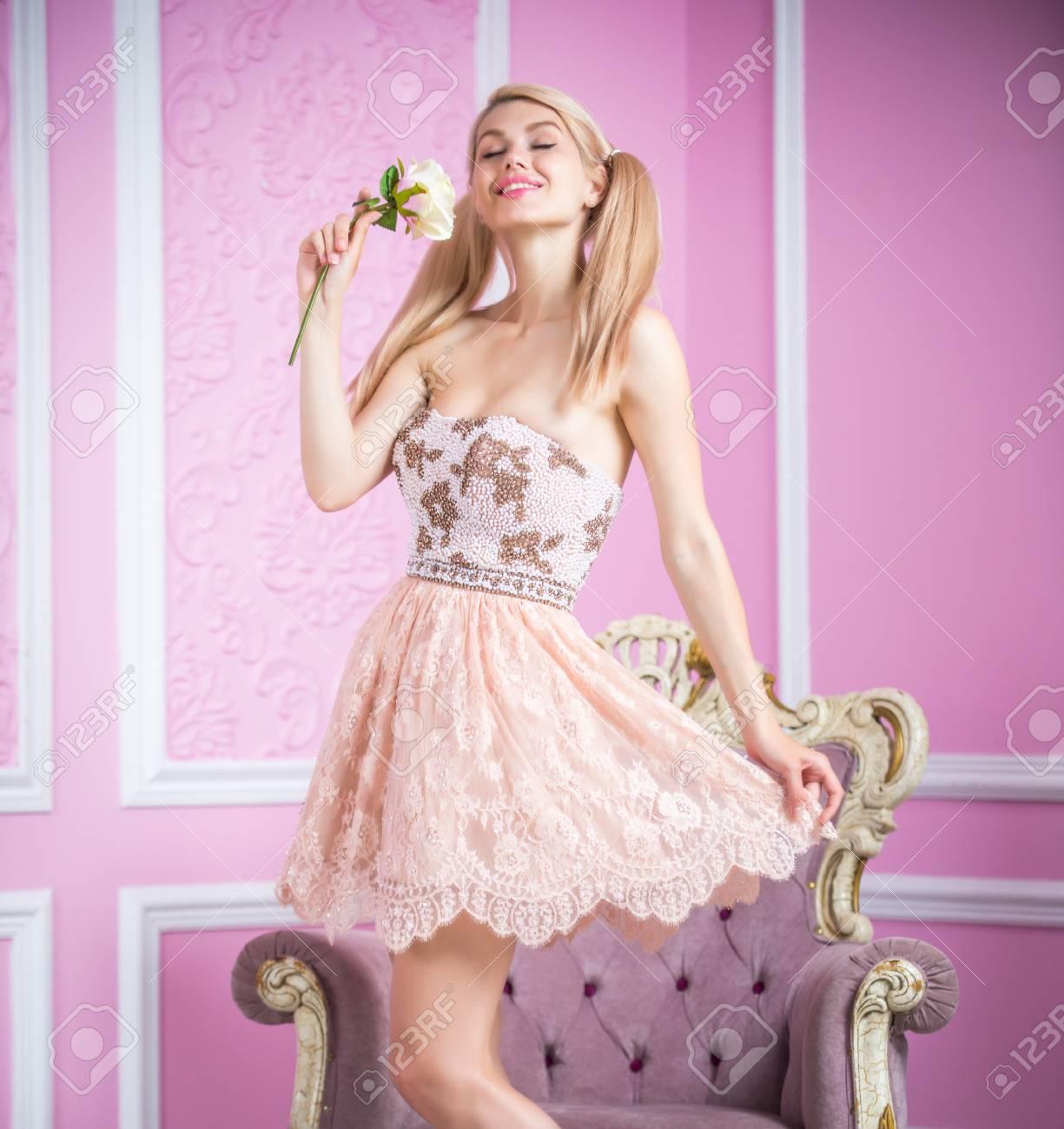 Schöne Blonde Sexy Frau Im Eleganten Kleid, Das Auf Einem Lehnsessel ...