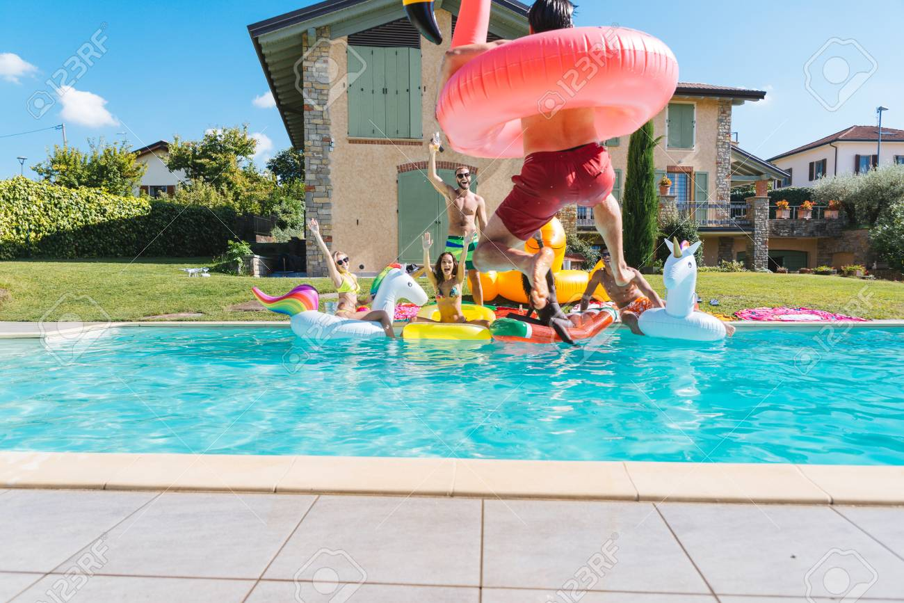 Multiracial group of friends having party in a private villa with swimming pool - Happy young people chilling with shaped air mattresses - 93302508