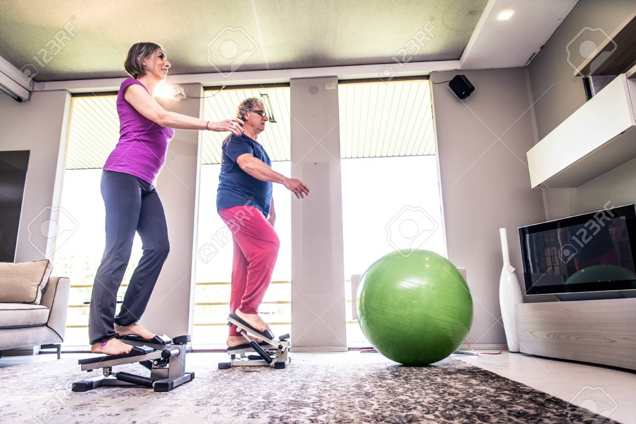 Retired people at exercise fitness activity in gym living room stock