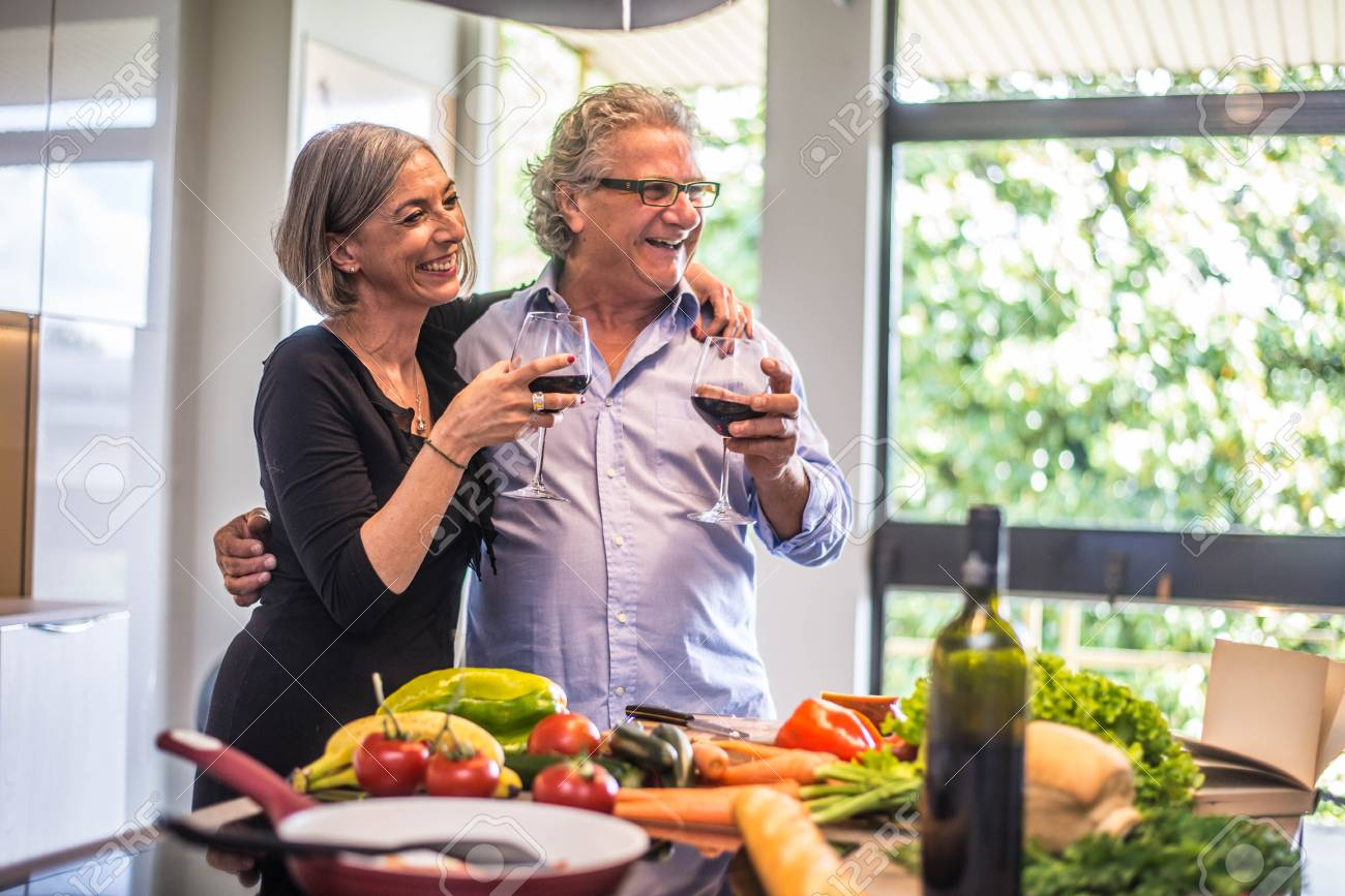 Senior couple cooking healthy food and drinking red wine at house kitchen - 94852206