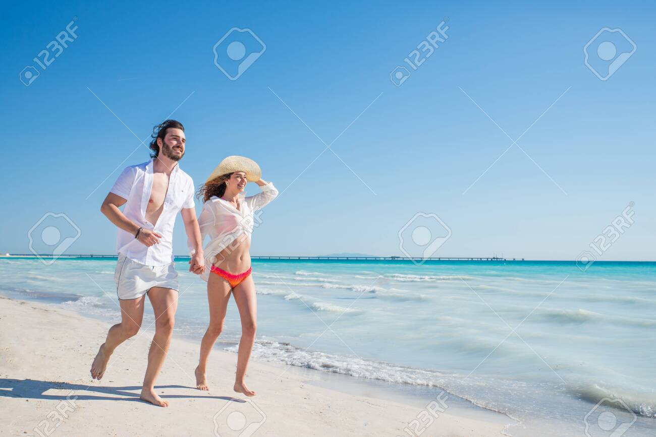 Couple strolling at the beach and smiling - Young adults enjoying summer holidays on a tropical island - 128952953