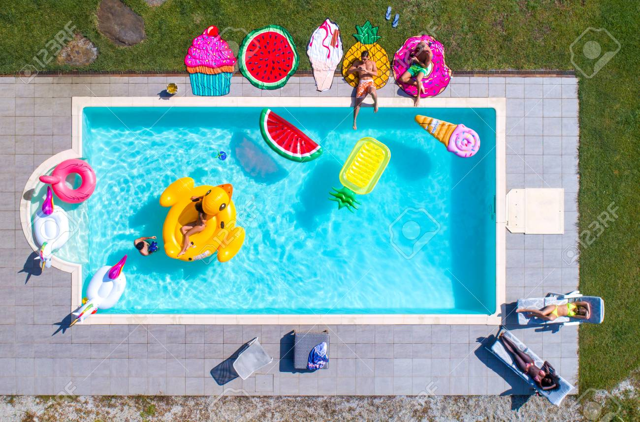 Happy people partying in an exclusive swimming pool with animal and fruit shapes mats, view from above - 102311676