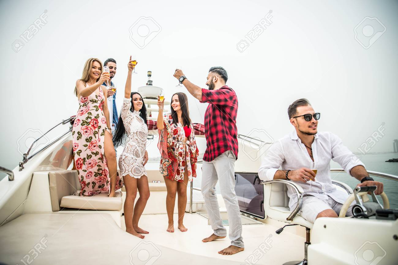 Group of friends making party on a yacht in Dubai - Happy people having a fancy party on a luxury boat - 105378611