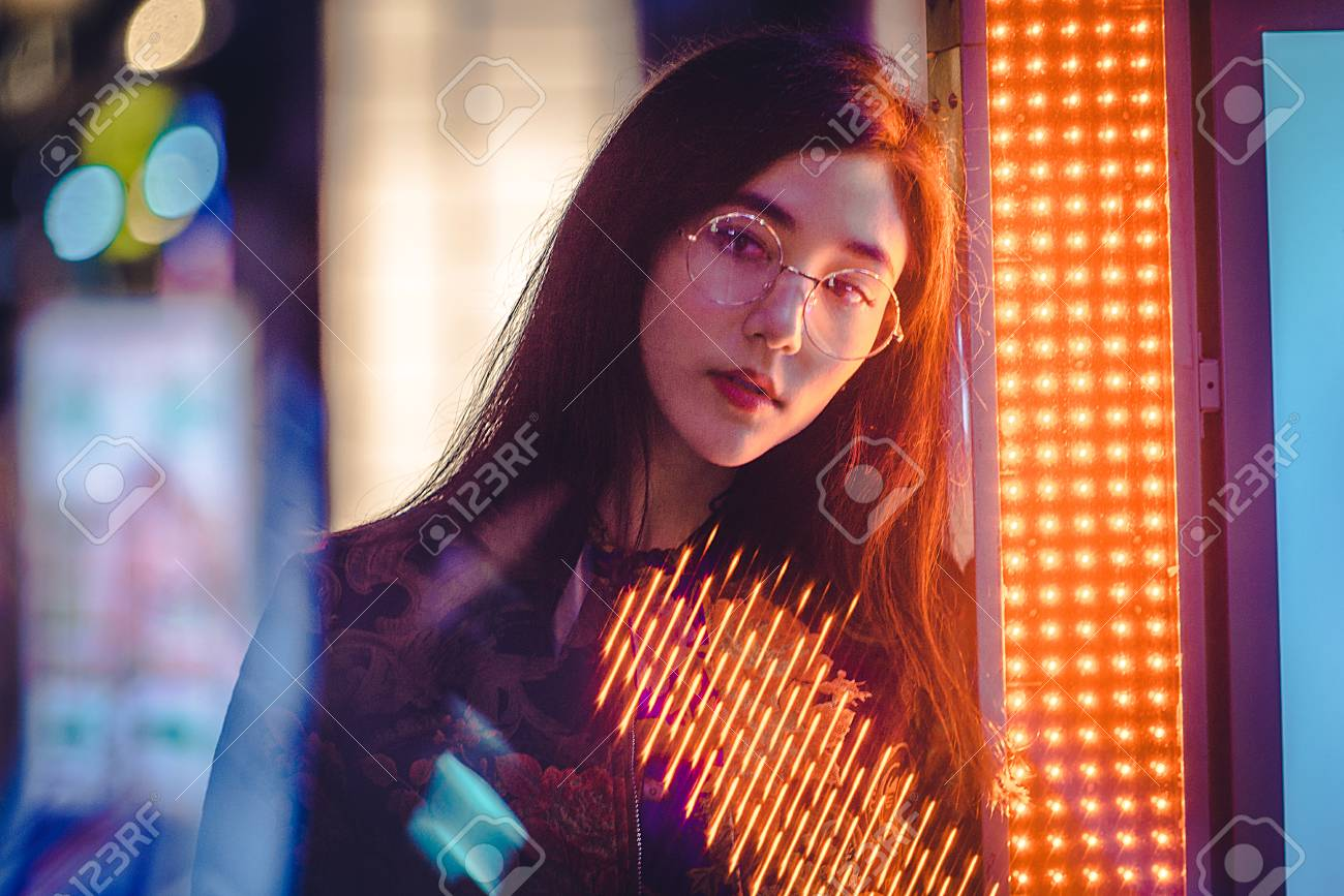 Beautiful mixed race woman posing outdoors, background with blurred neon lights - 114130208
