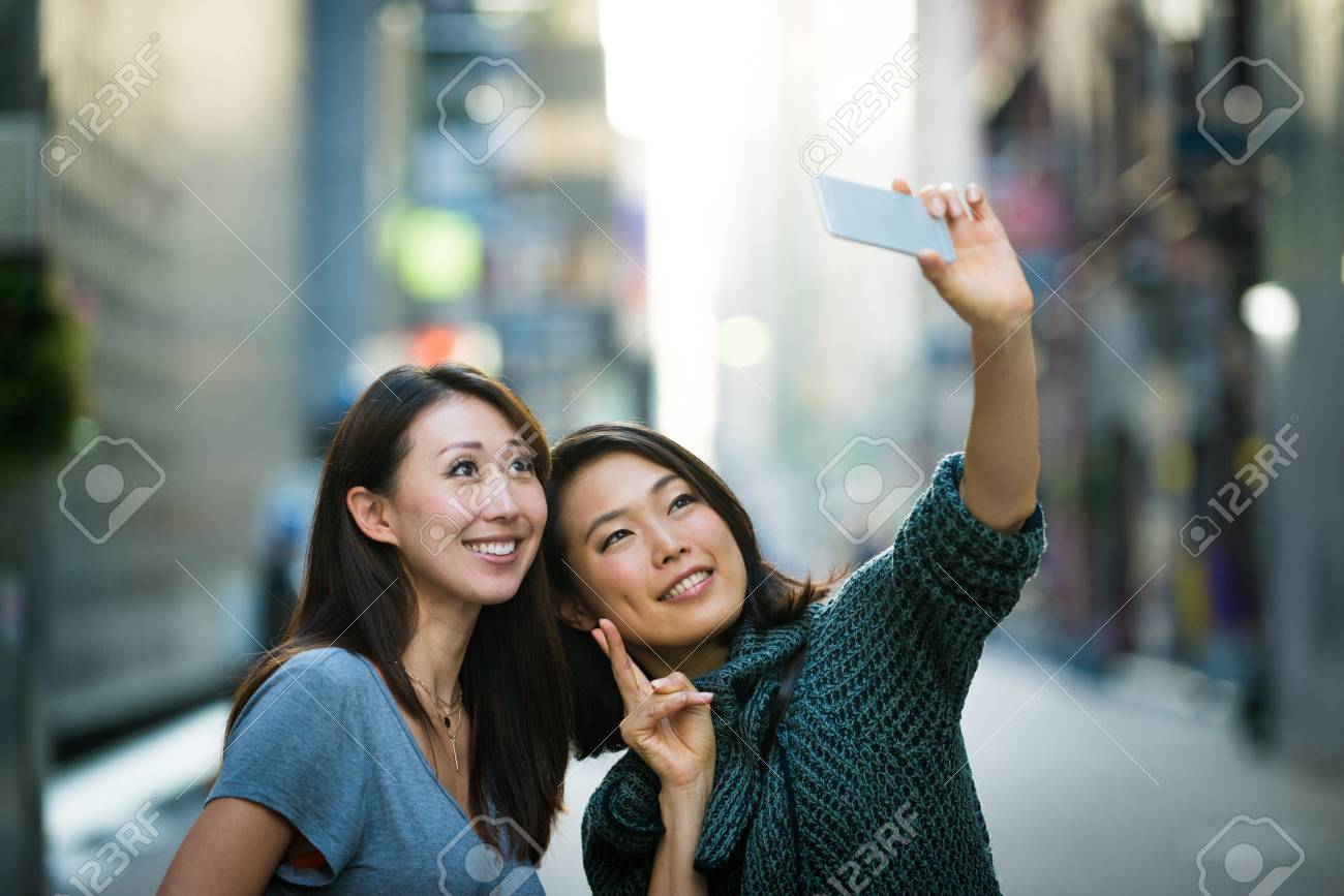Two girlfriends meeting outdoors and having fun - Japanese people bonding on Tokyo streets - 114130538