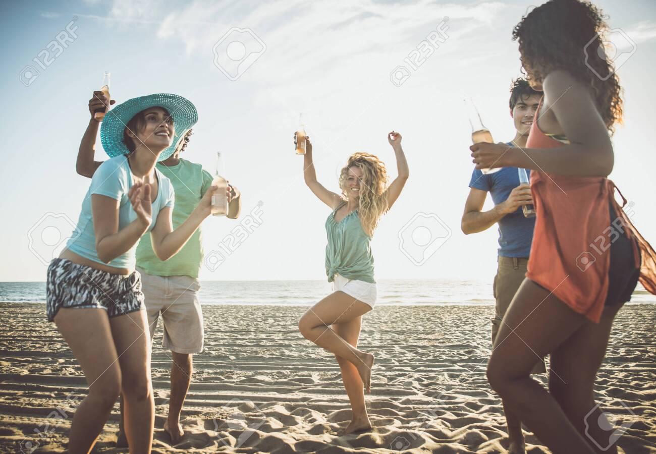 Group of friends having fun on the seashore - 128424102
