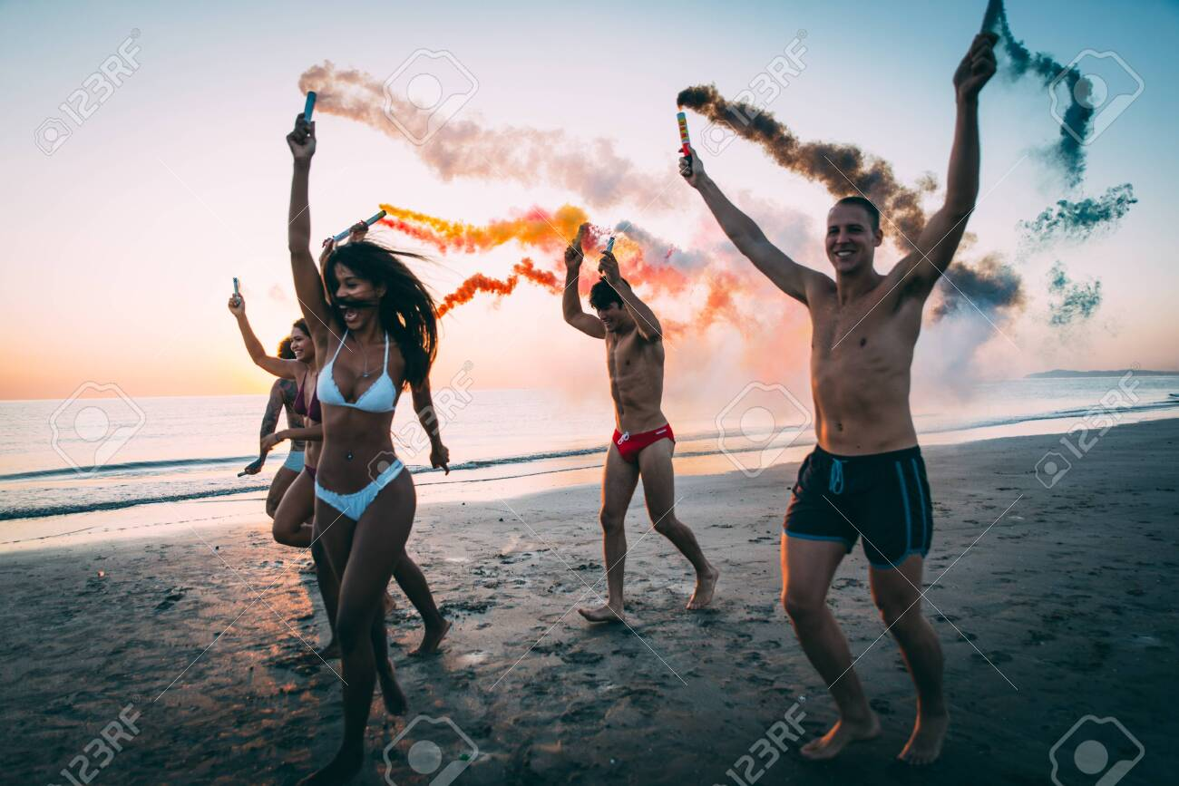 Group of friends having fun running on the beach with smoke bombs - 128421883
