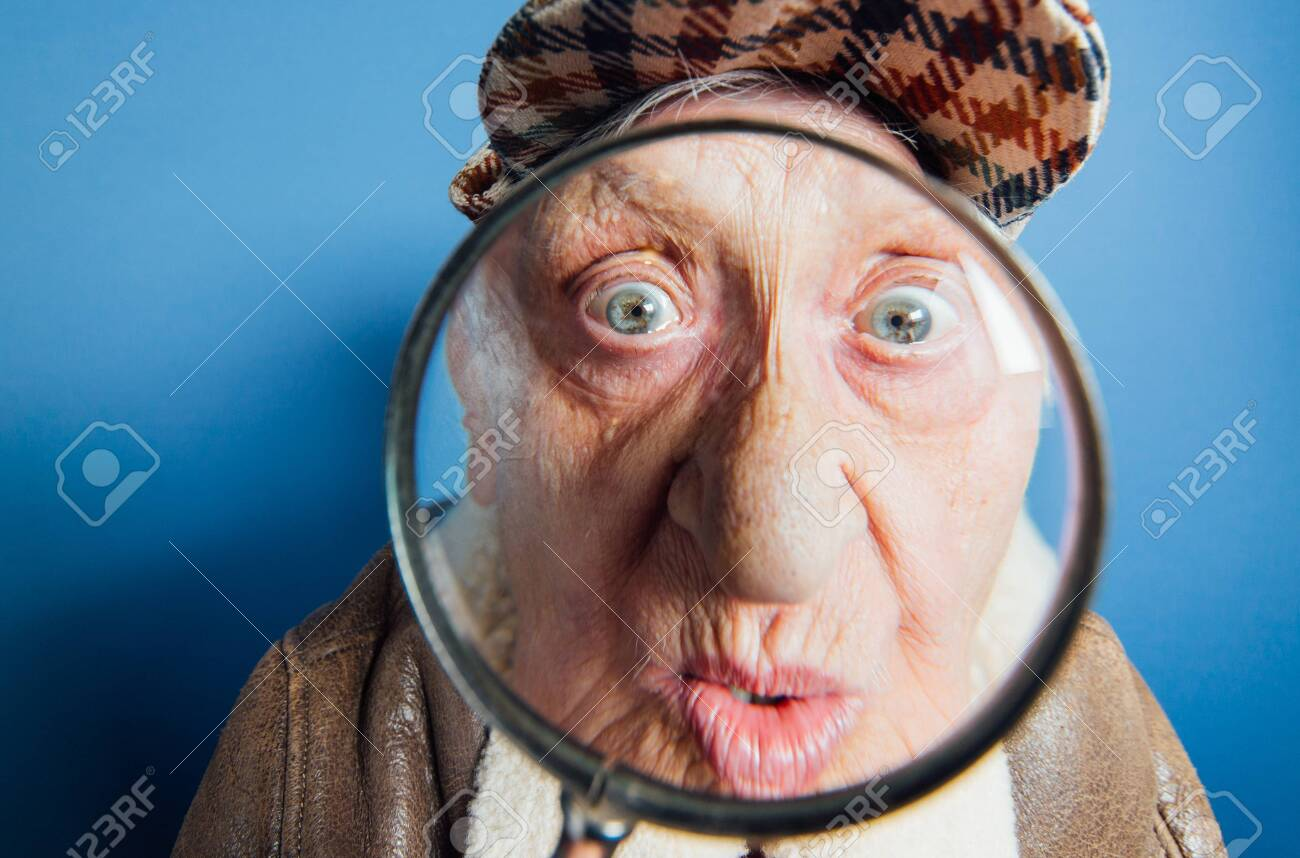 Funny portraits with old grandmother. Senior woman acting as an investigator with the magnifying lense - 132081260