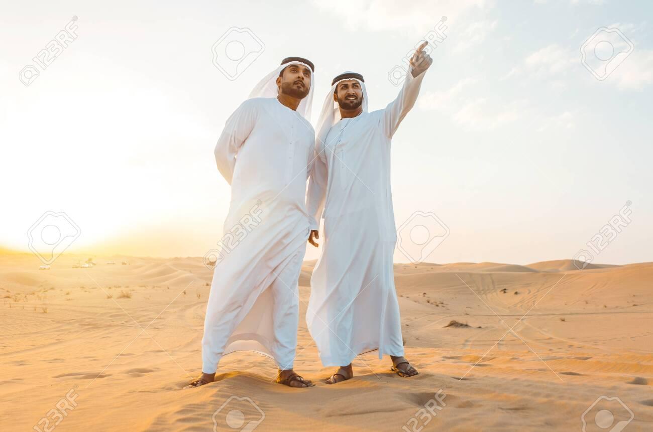 Two business men wearing traditional uae white kandura spending time in the desert of Dubai - 137877369