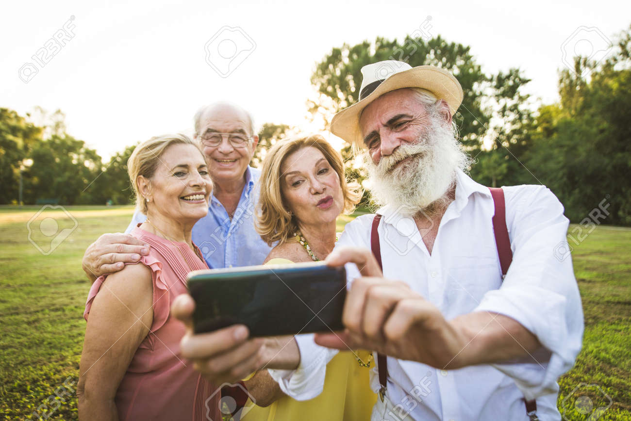 Group of youthful seniors having fun outdoors - Four pensioners bonding outdoors, concepts about lifestyle and elderly - 155169552
